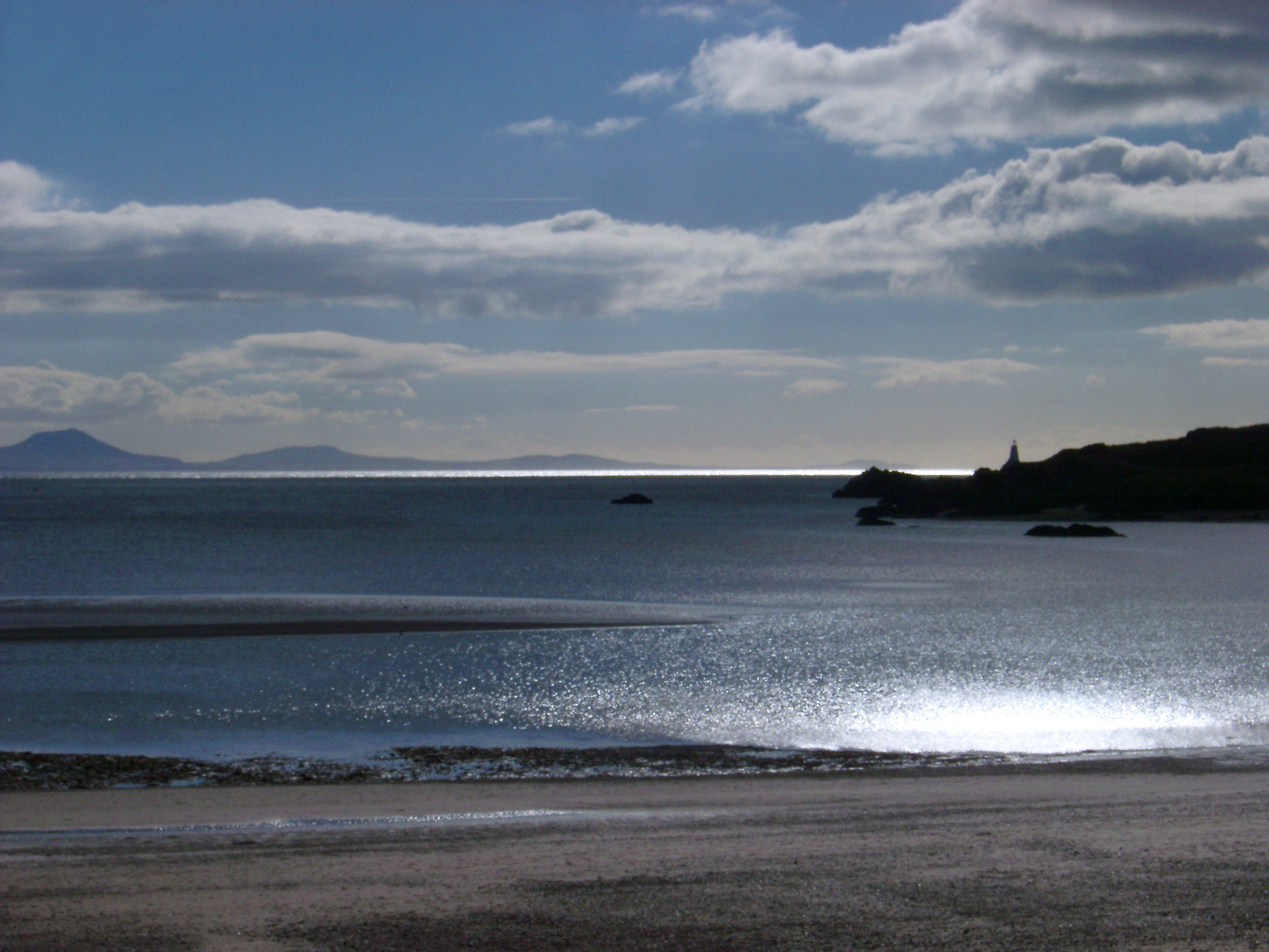 Silhouette View Towards the Welsh Mainland from Romantic Beach of Llanddwyn Island During Afternoon.