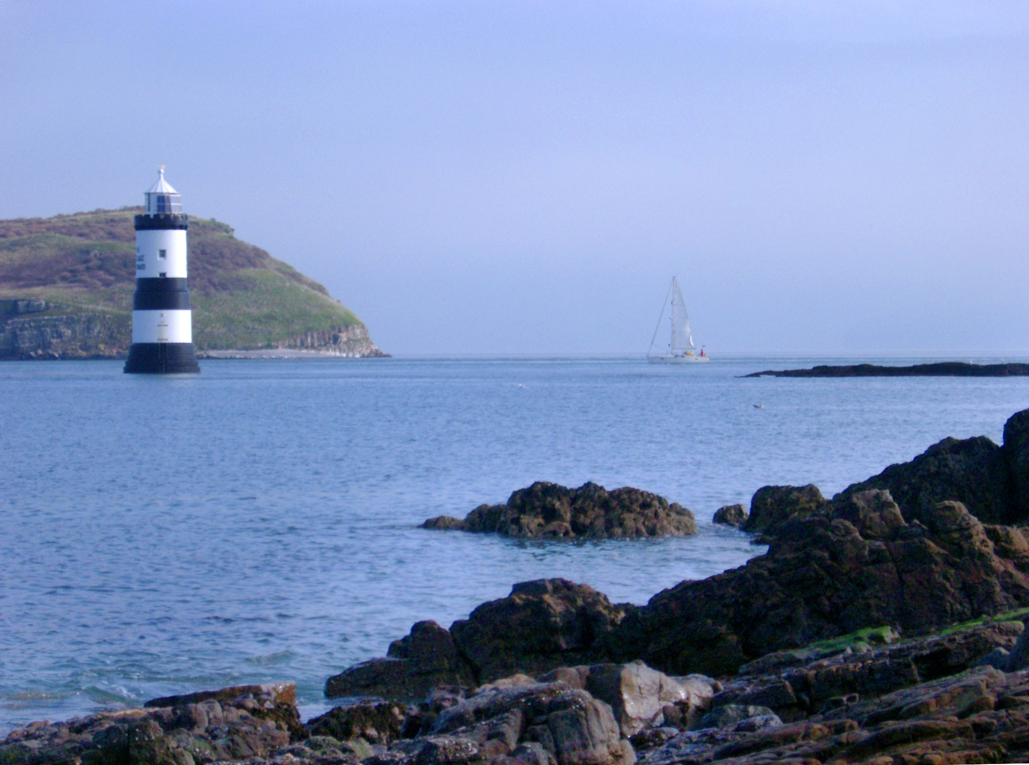Lighthouse off a headland on the coast of Anglesey, Wales to warn shipping of a hazard