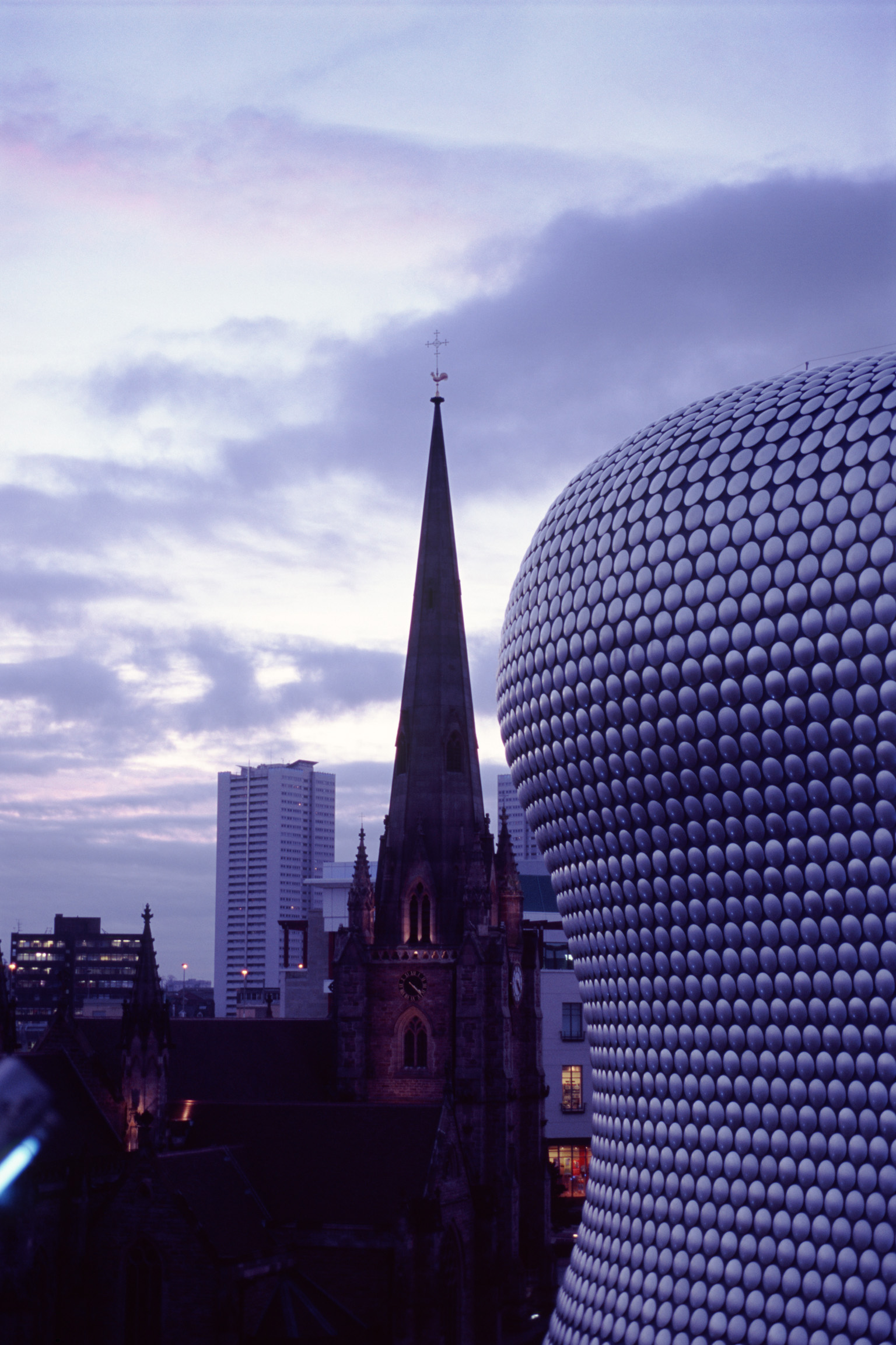 Modern curved exterior facade of the Bullring Shopping Centre with St Martins spire in the background at dusk, Birmingham, UK