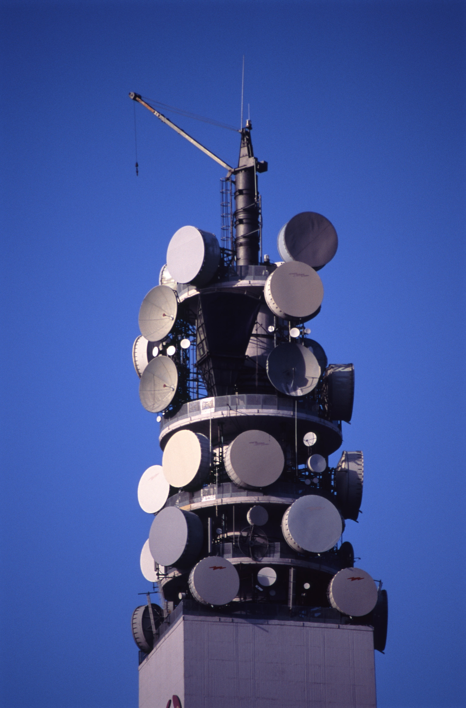Telecommunications tower with dishes and antennae for reception and broadcasting of wireless radio waves against a clear blue sky