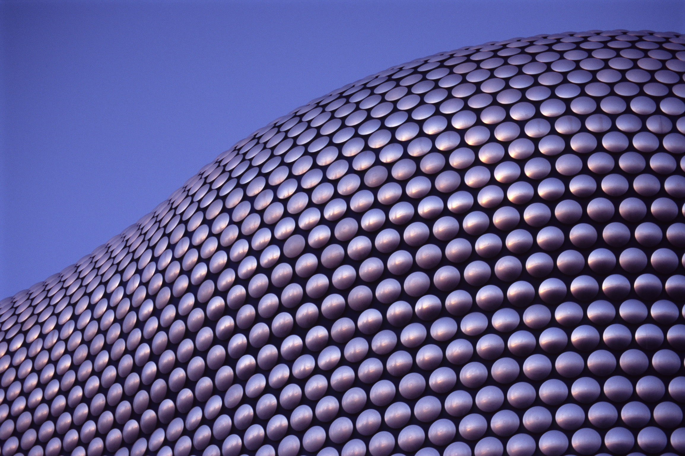 Close up on the cladding of the Selfridges Building at Birmingham Bullring Shopping Center on a Sunny Day with Blue Gray Sky Background.