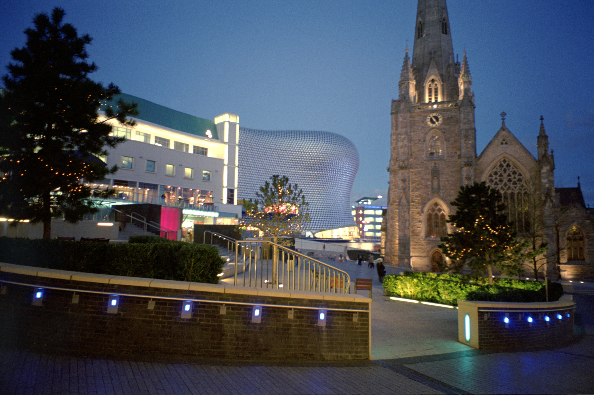 View of an urban square with church and spire in central Birmingham with the Bullring shopping centre in the background at night