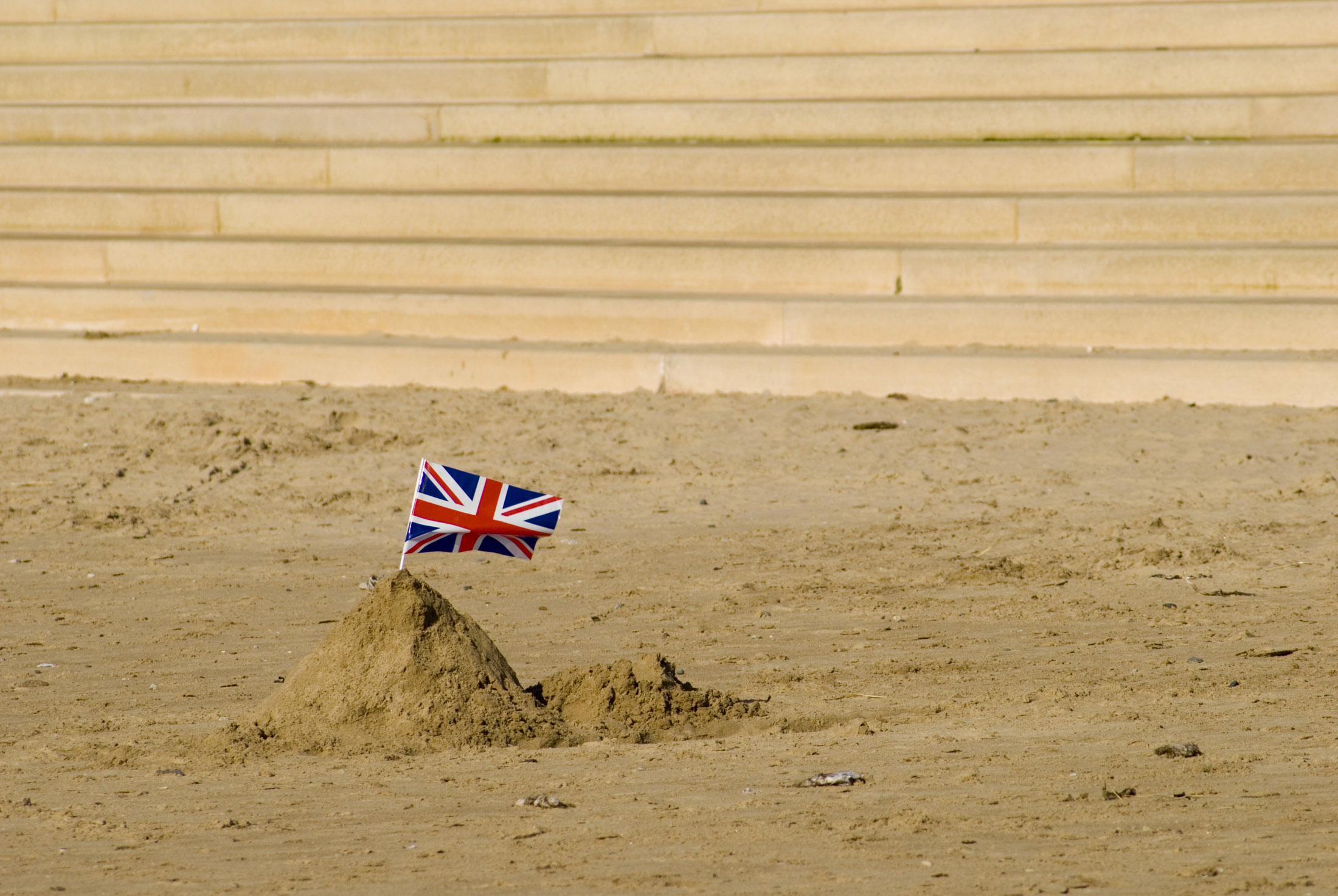 a simple sand castle with a union jack stuck in it