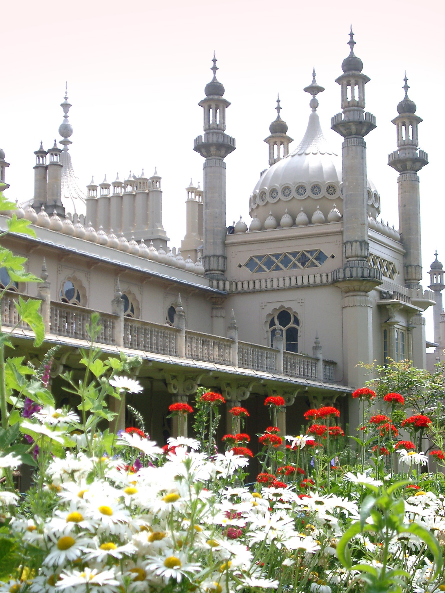 Onion dome and minarets of the Brighton Royal Pavilion viewed across a bed of summer flowers with white daisies in the foreground