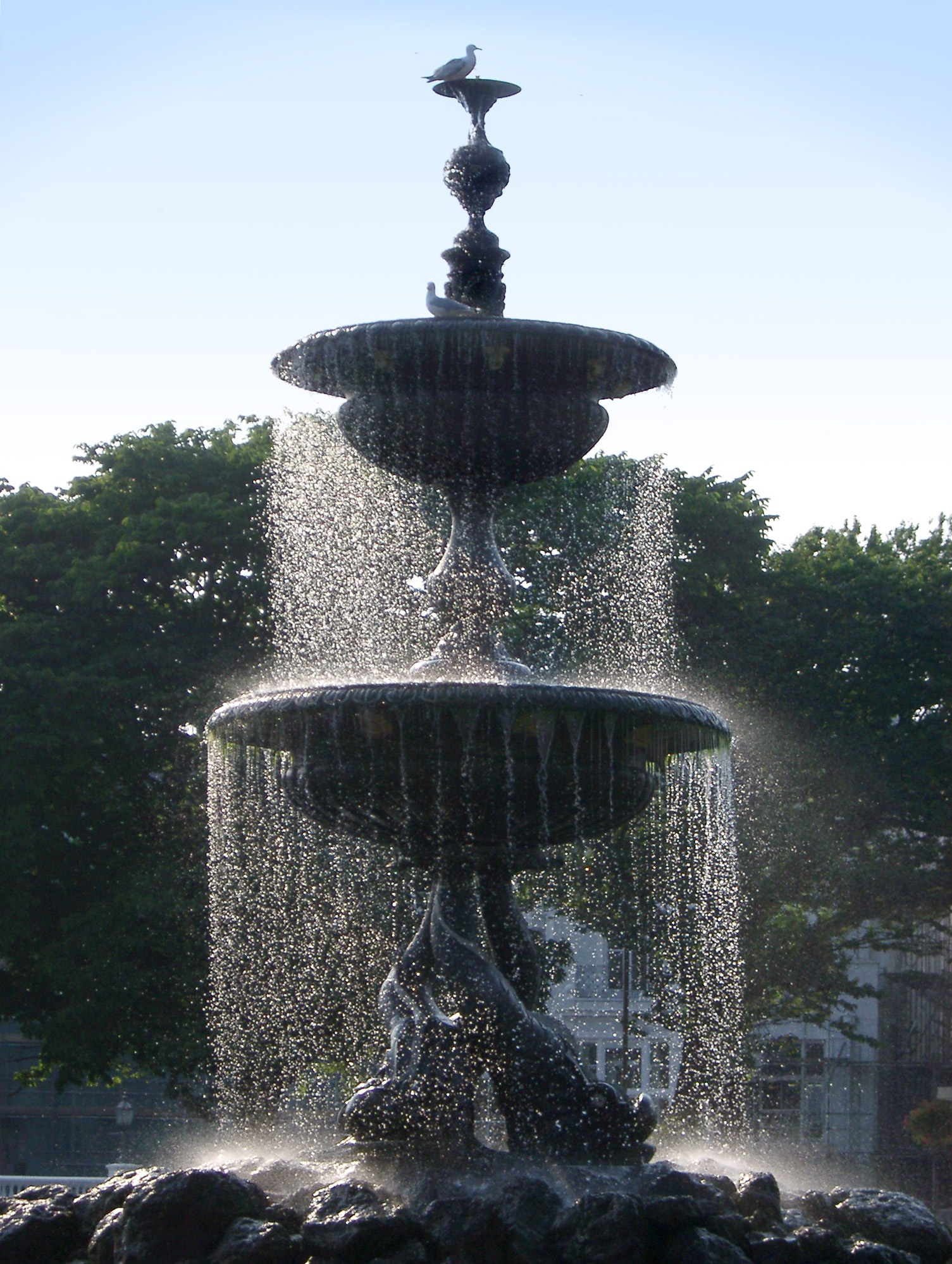 Ornamental Brighton stone fountain with falling curtains of water and pigeons enjoying the cool spray on a hot day