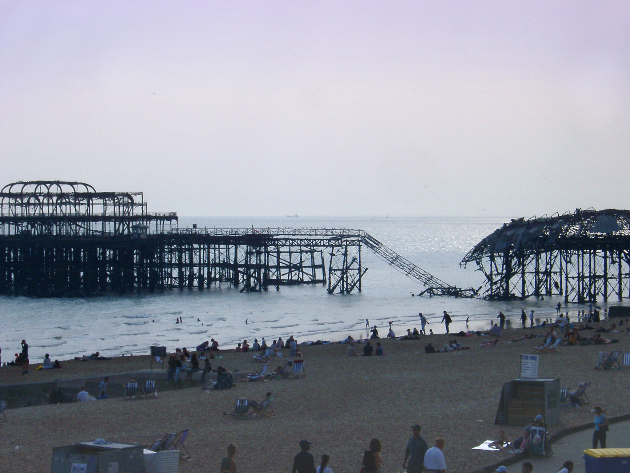 Remnants of the badly damaged fire damaged Brighton pier partially collapsed into the sea with people on the beach in the foreground