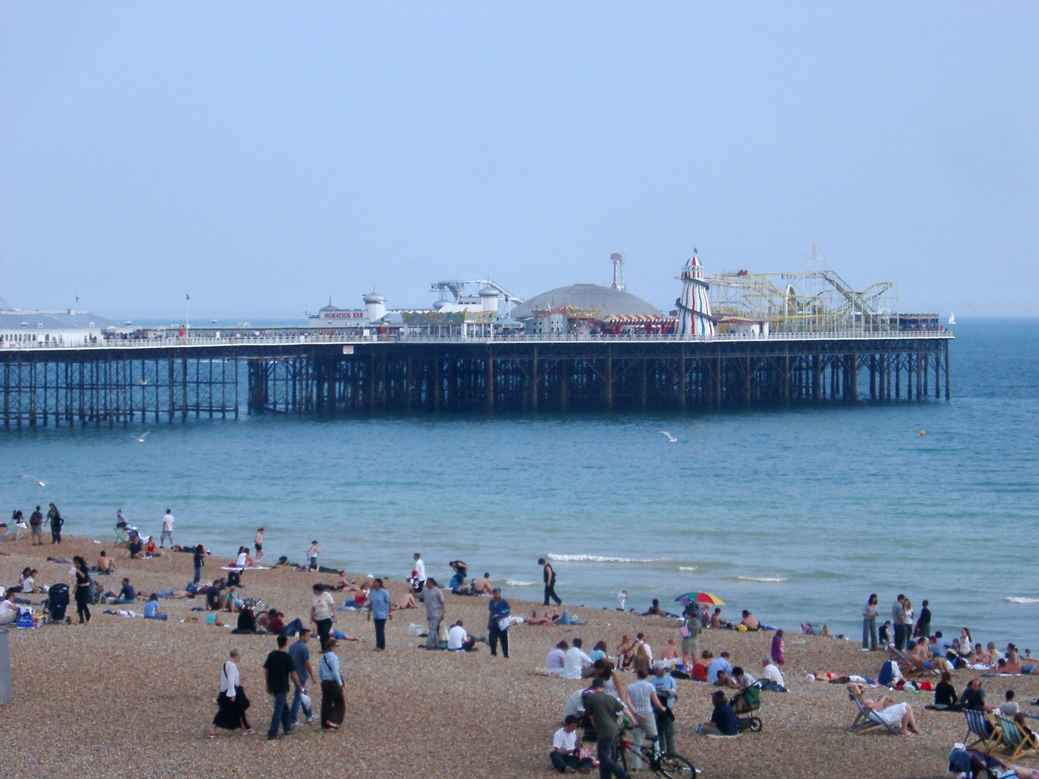 View from the beach of Brighton pier with its amusement arcade and historical buildings which are a popular tourist venue, people in the foreground on the sand