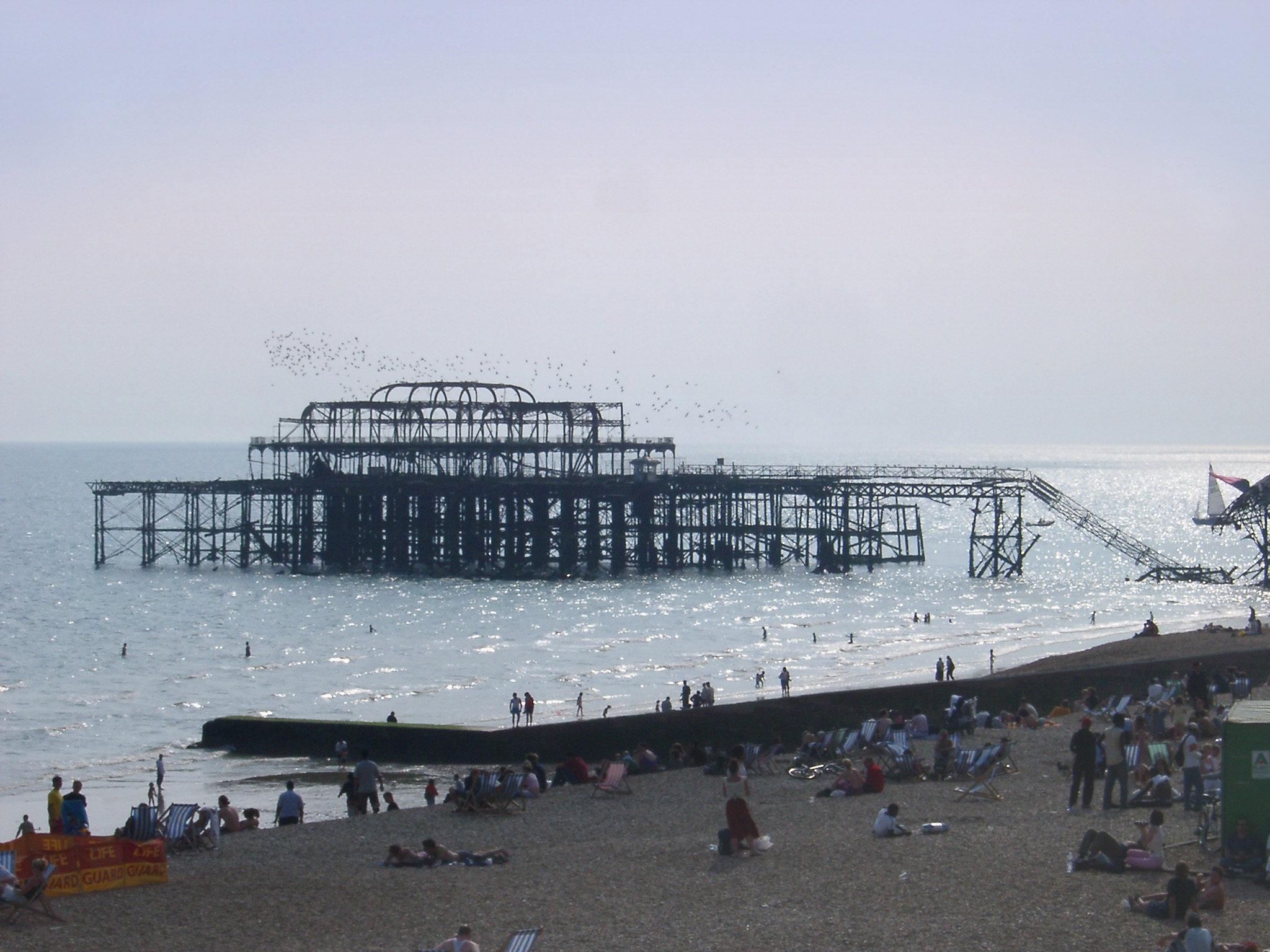 Famous Old Damaged West Pier Due to Heavy Storms in 1975 at Brighton, England. Captured with Tourist Relaxing on the Beach.