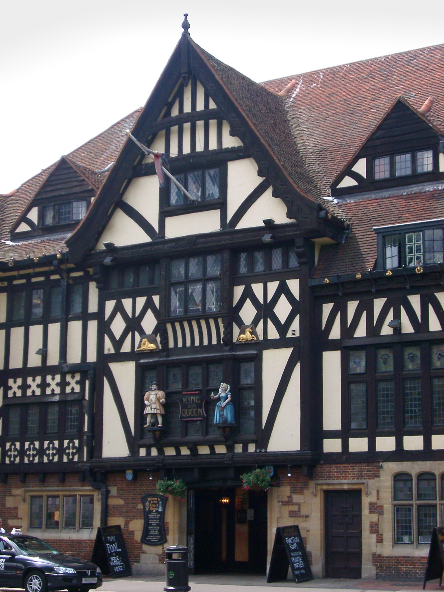 Tudor frame pub facade showing the traditional exterior timber framework on the white walls with two statues above the entrance and menus displayed in the street