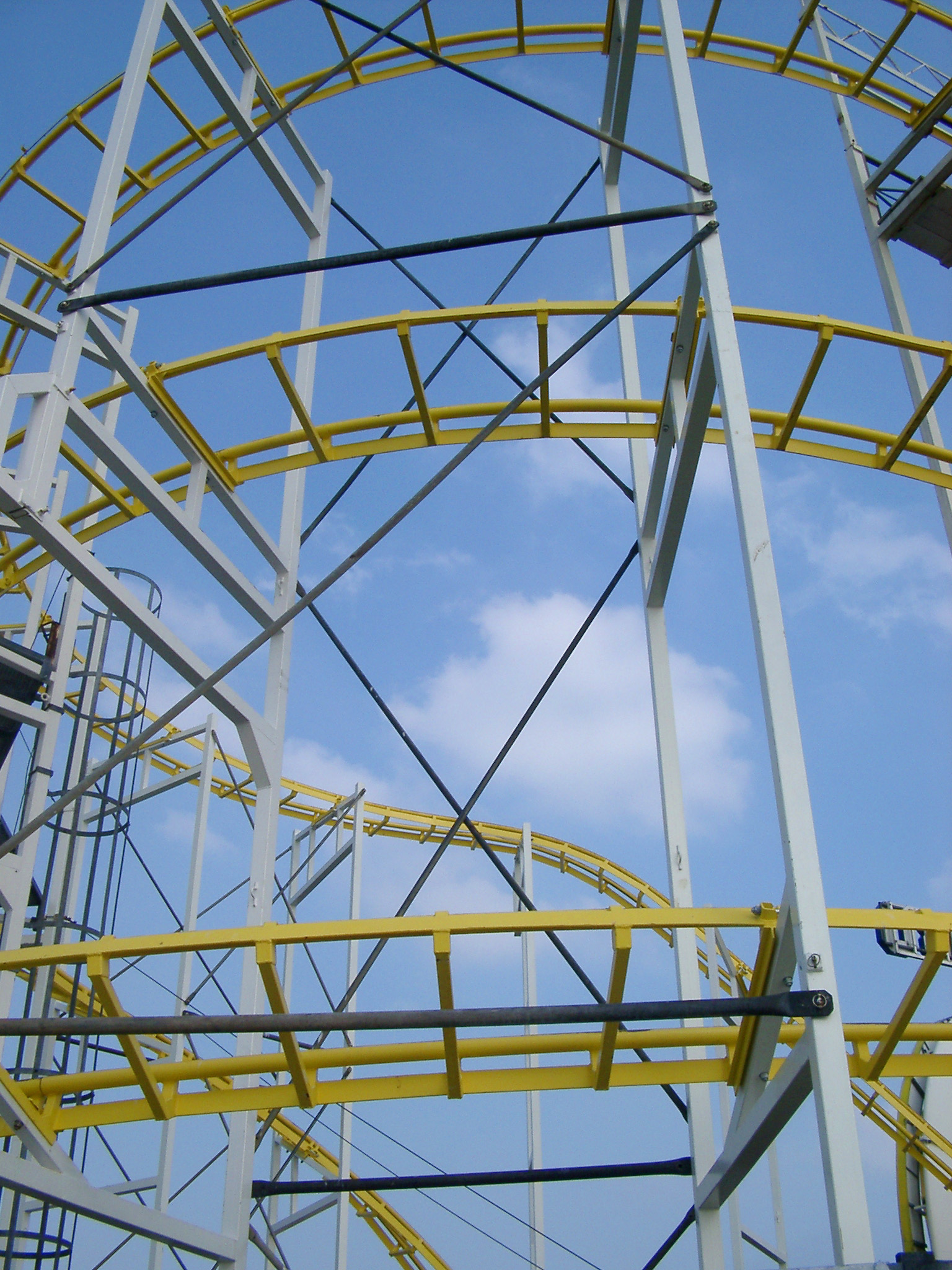 Details of the metal framework of a roller coaster ride at an amusement park against a sunny blue sky