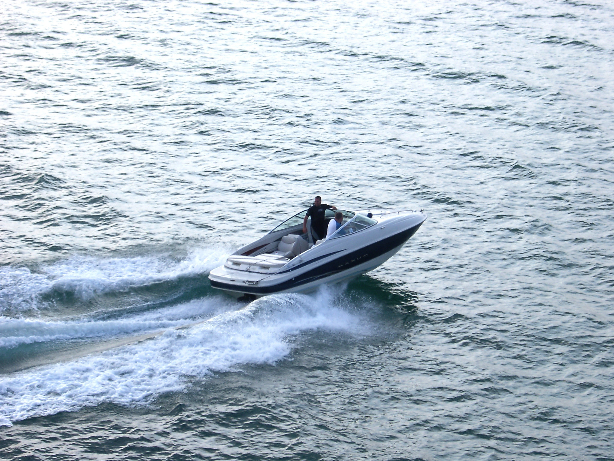 Aerial View of Man Travelling in a Small Speed Boat at Brighton Sea, England.