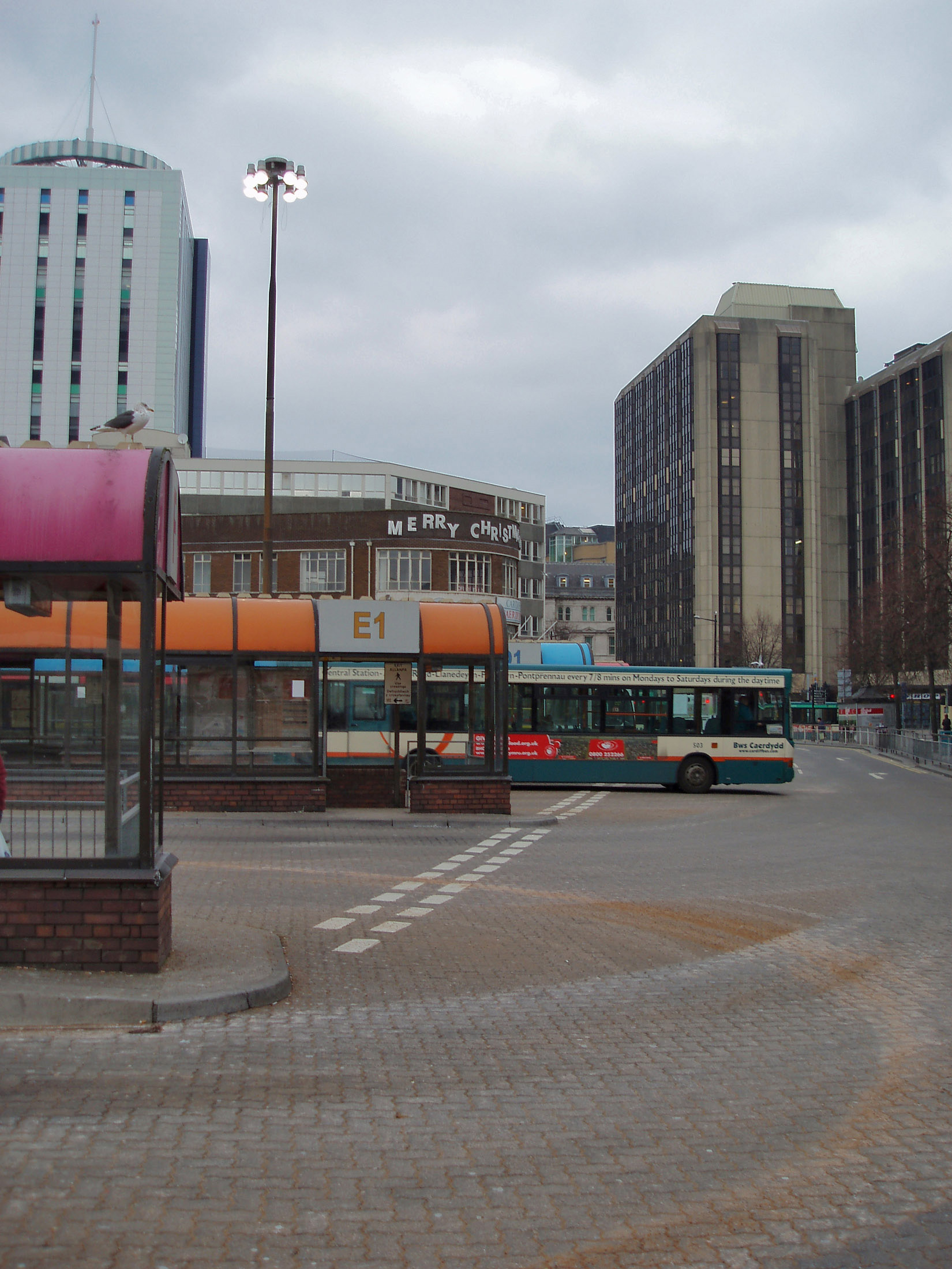 Depressing view of the Central Bus Station in Cardiff with rows of shelters and a departing bus on a dismal grey cloudy day