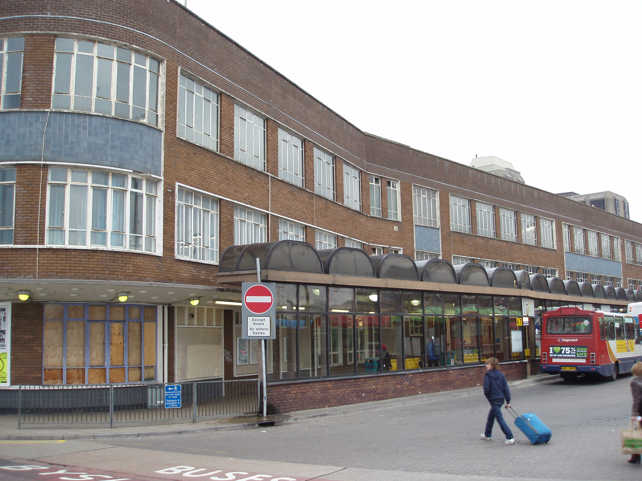 View of the Central Bus Station, Cardiff, Wales with a row of shelters along the exterior of the depot and a woman walking past with her suitcase as a bus loads passengers in the background
