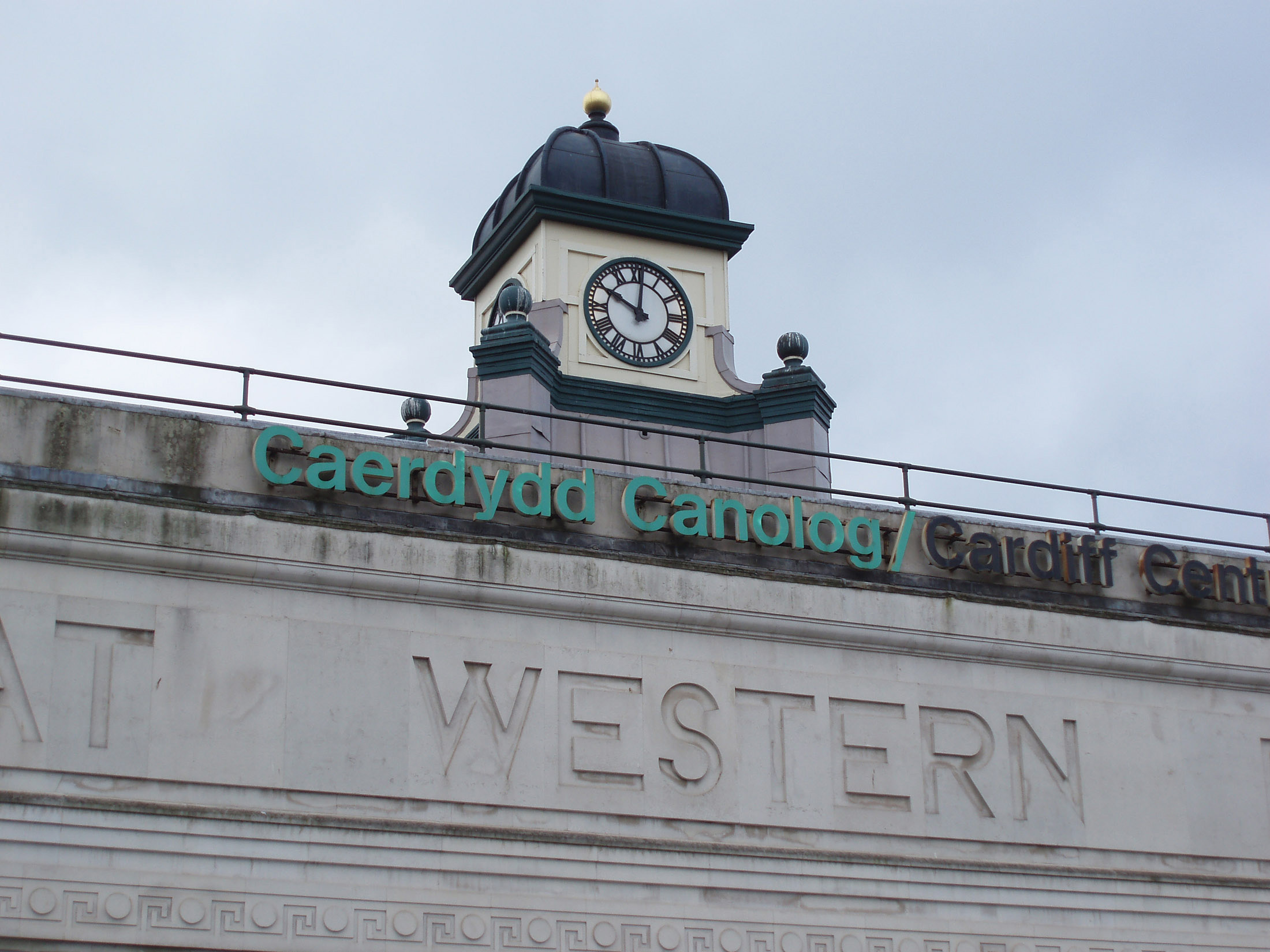Old Clock on Top of the main Building with Carvings on the Wall at Cardiff Central Station, Wales.