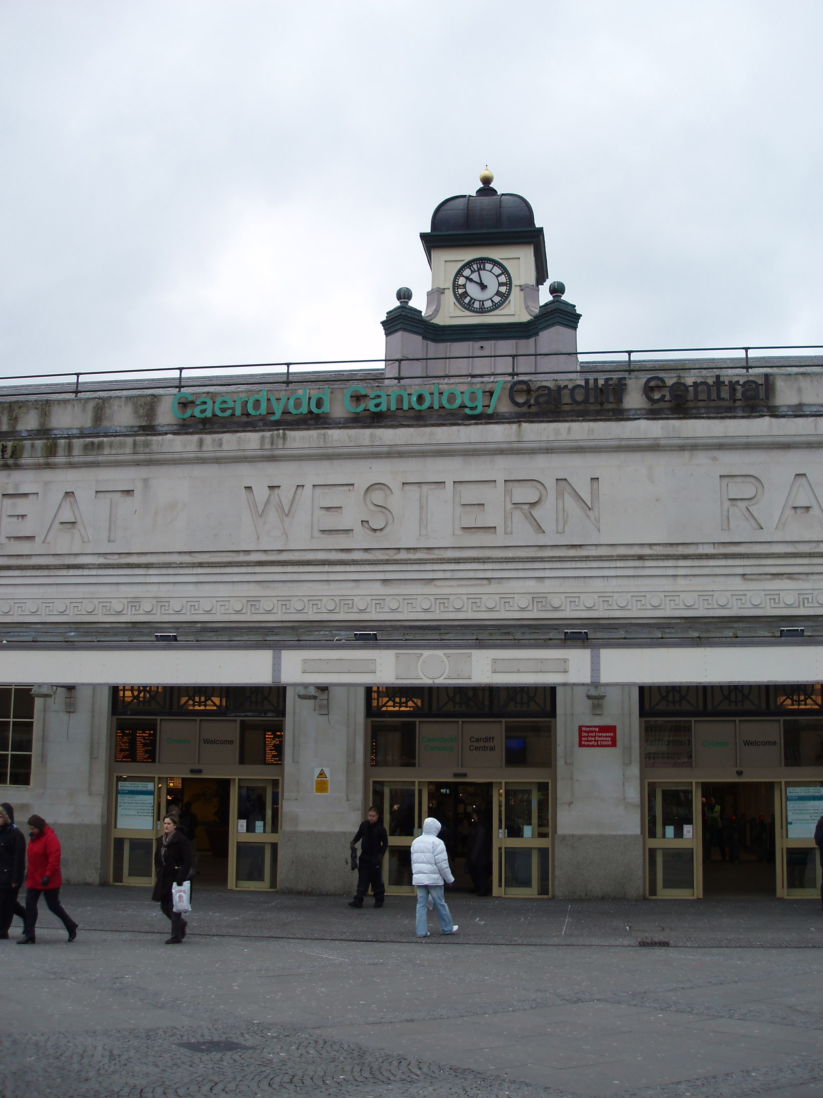 Cardiff Central Station with the clock tower above and Great Western Railway on the building facade, people entering the doors