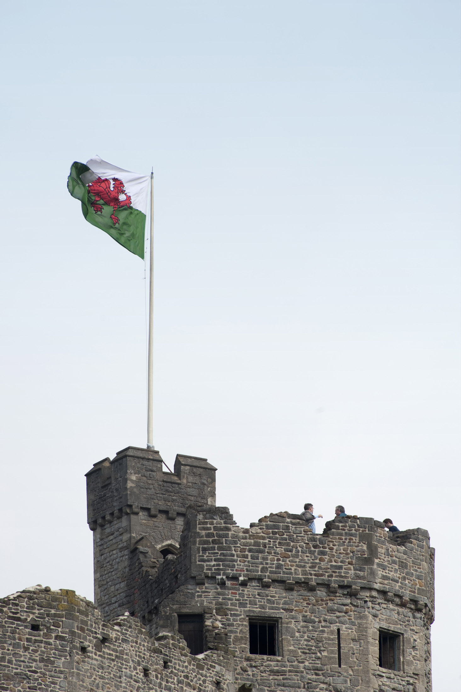 the welsh national flag flying proudly from the top of cardiff castle