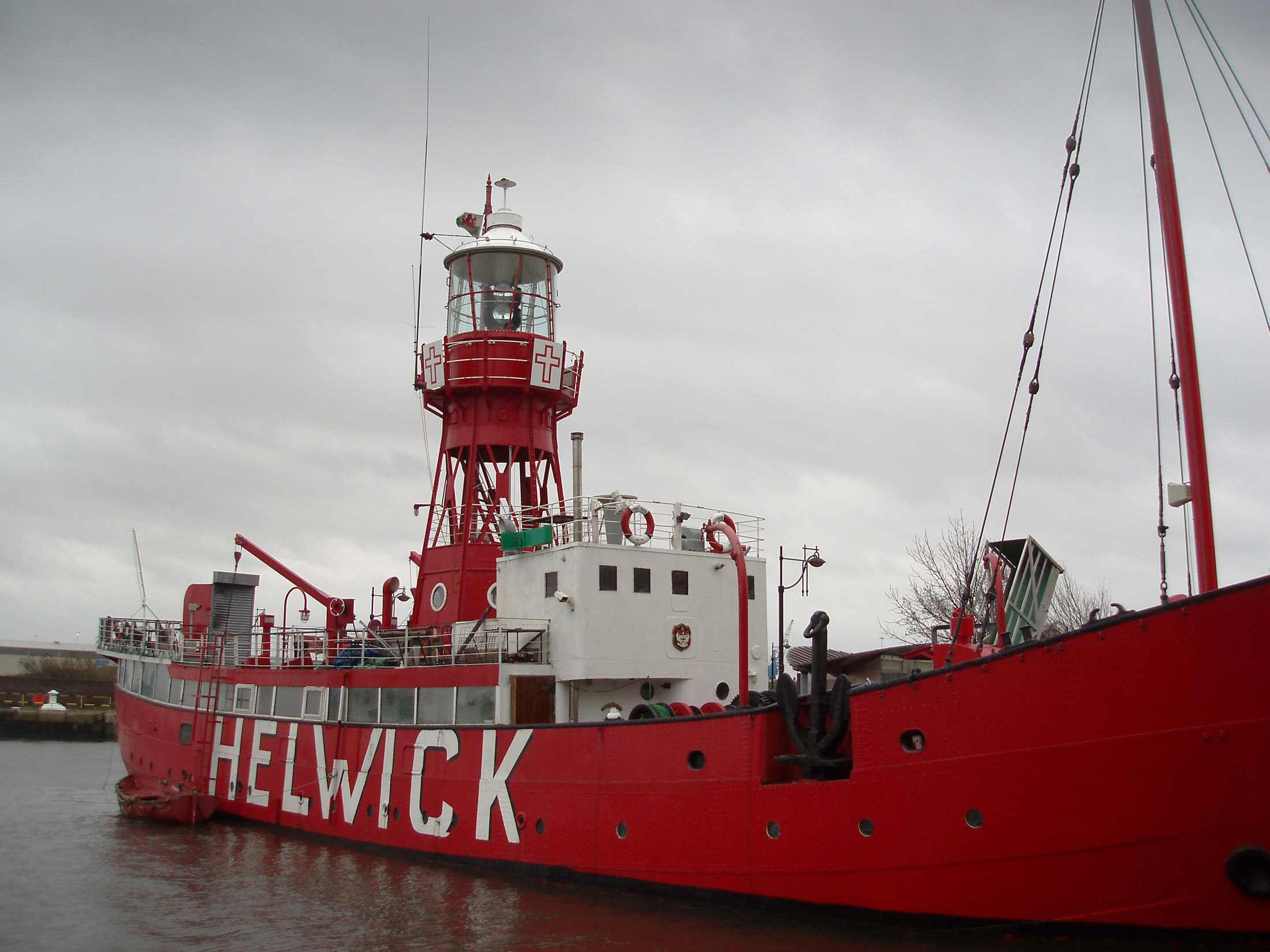 Historical Red Helwick Lightship at the Dock of Cardiff Bay, Wales. Captured on a Gray Sky Background.