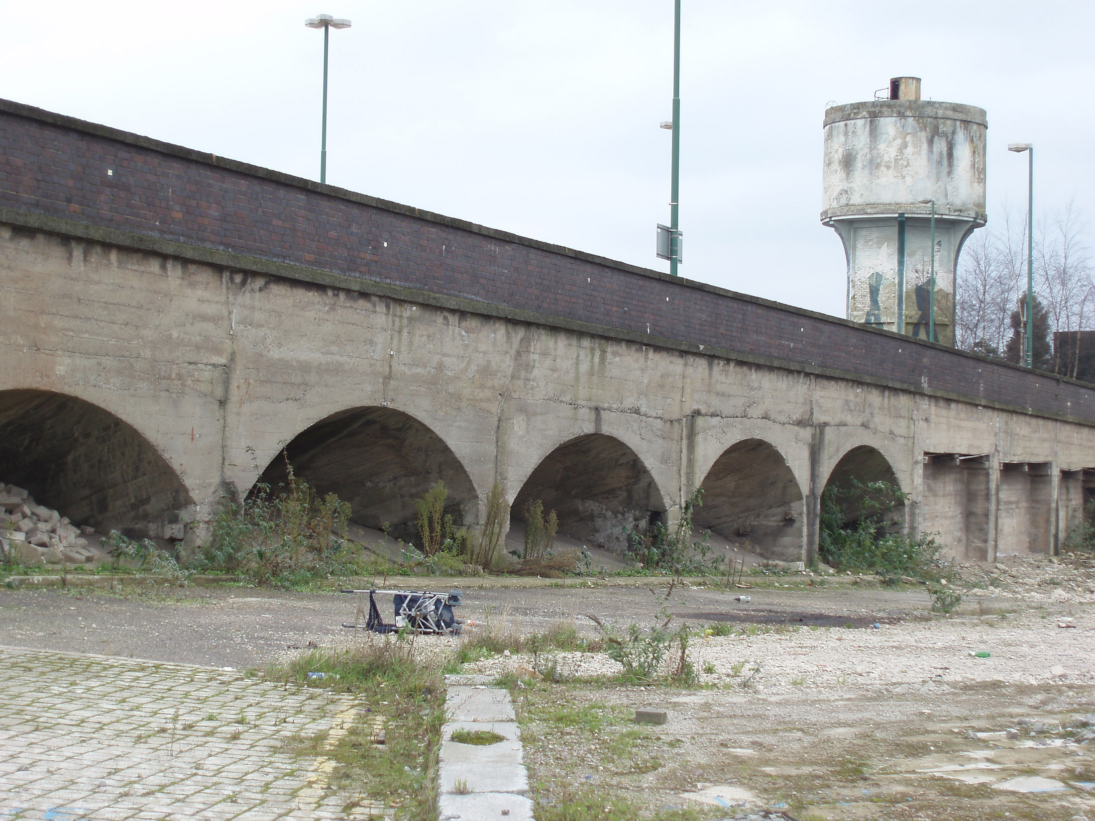 Old grungy obsolete railway bridge with arches in urban wasteland with a concrete water tower