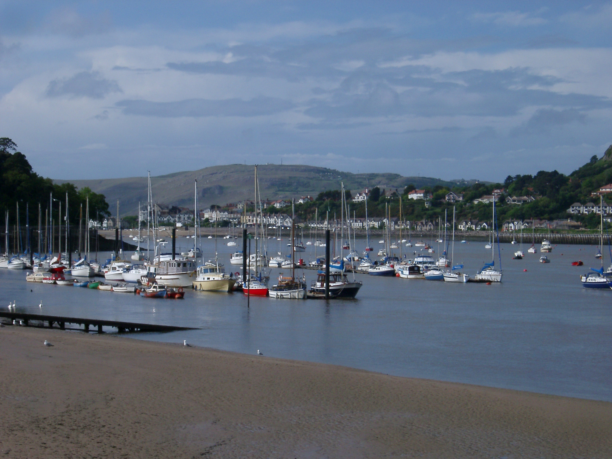 Fishing and pleasure boats moored in the sheltered water of the estuary on the Conway River , Wales