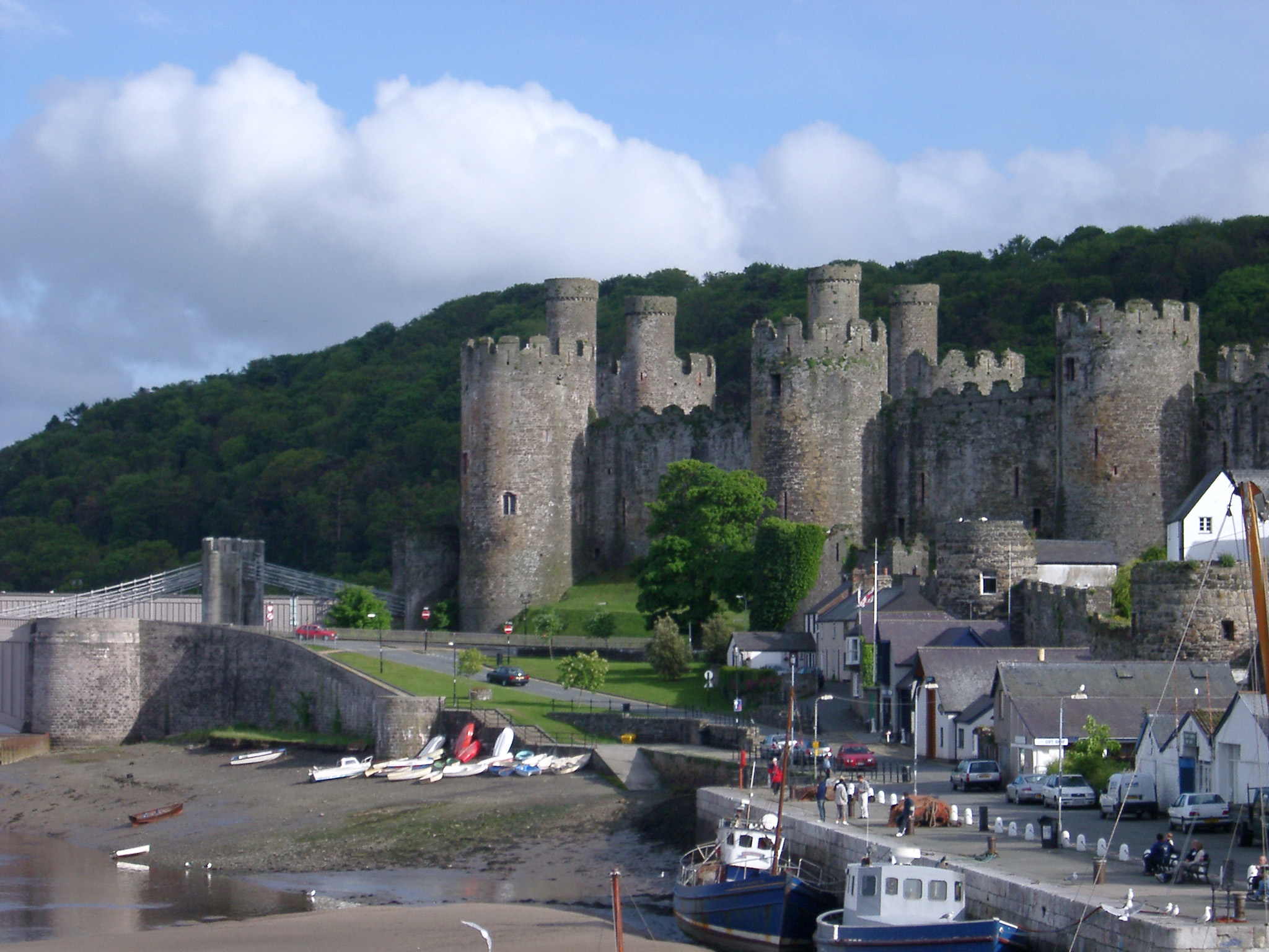 view of historic conwy castle and fishing boats at a jetty on the banks of the conwy river