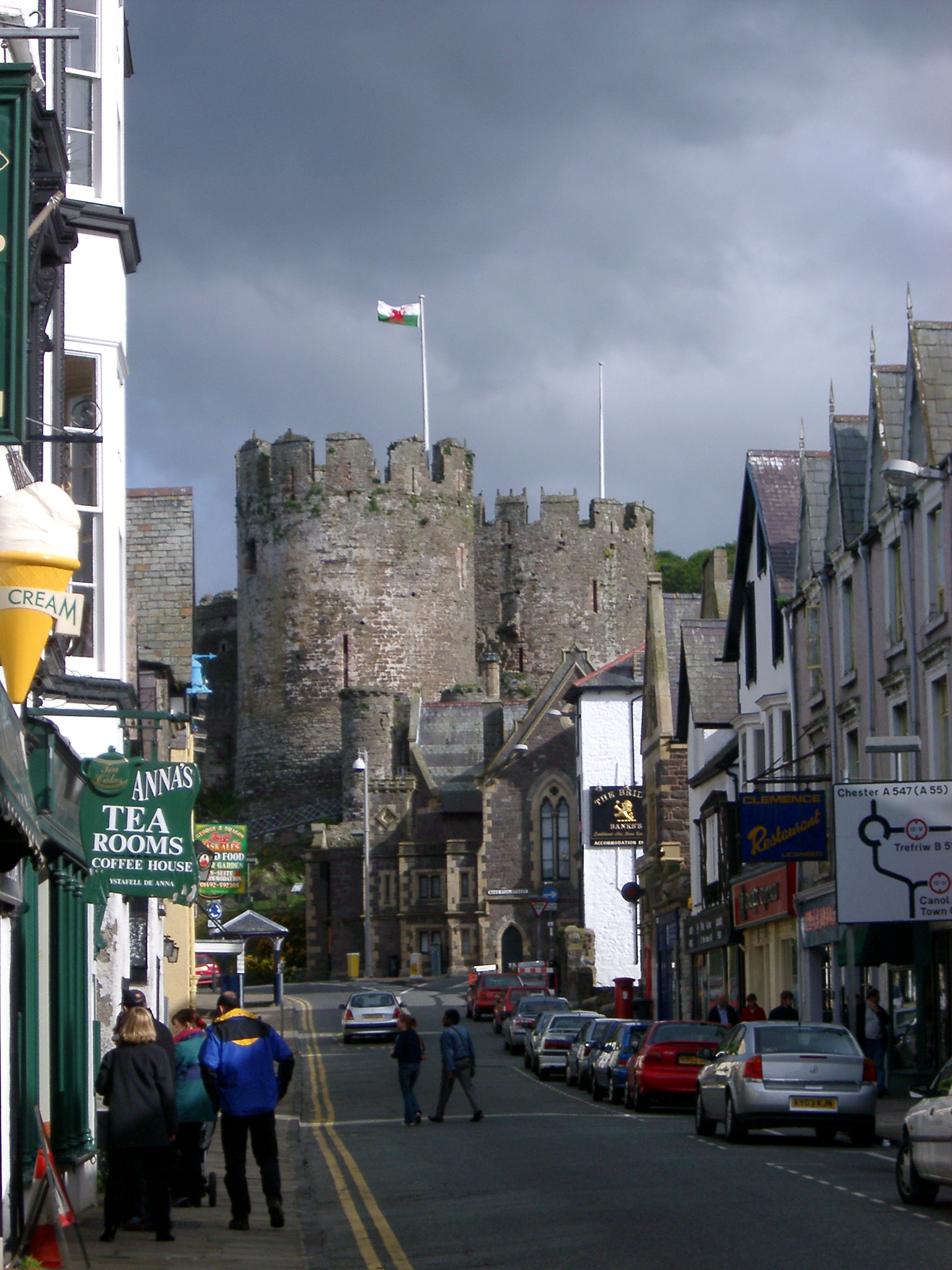 Busy Street Scene with Vehicles and People at Conwy, Wales. Captured with the Castle on a Stormy Sky Above.
