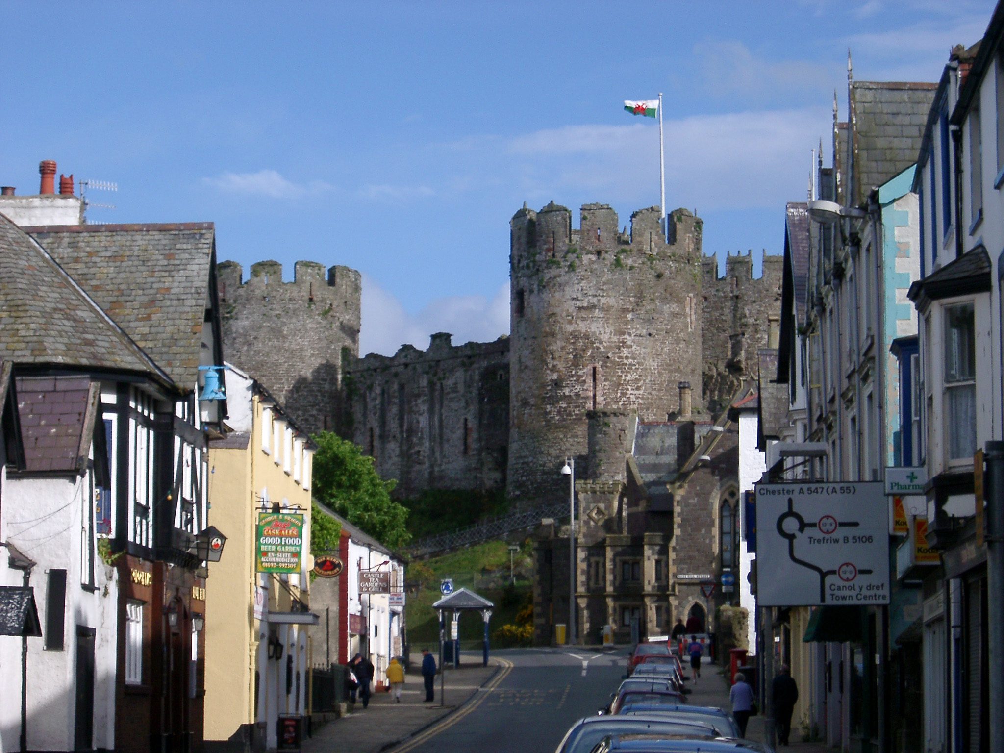 Street scene in Conway, Wales with a road sign, quaint historical buildings and the towers of the medieval stone castle in the background