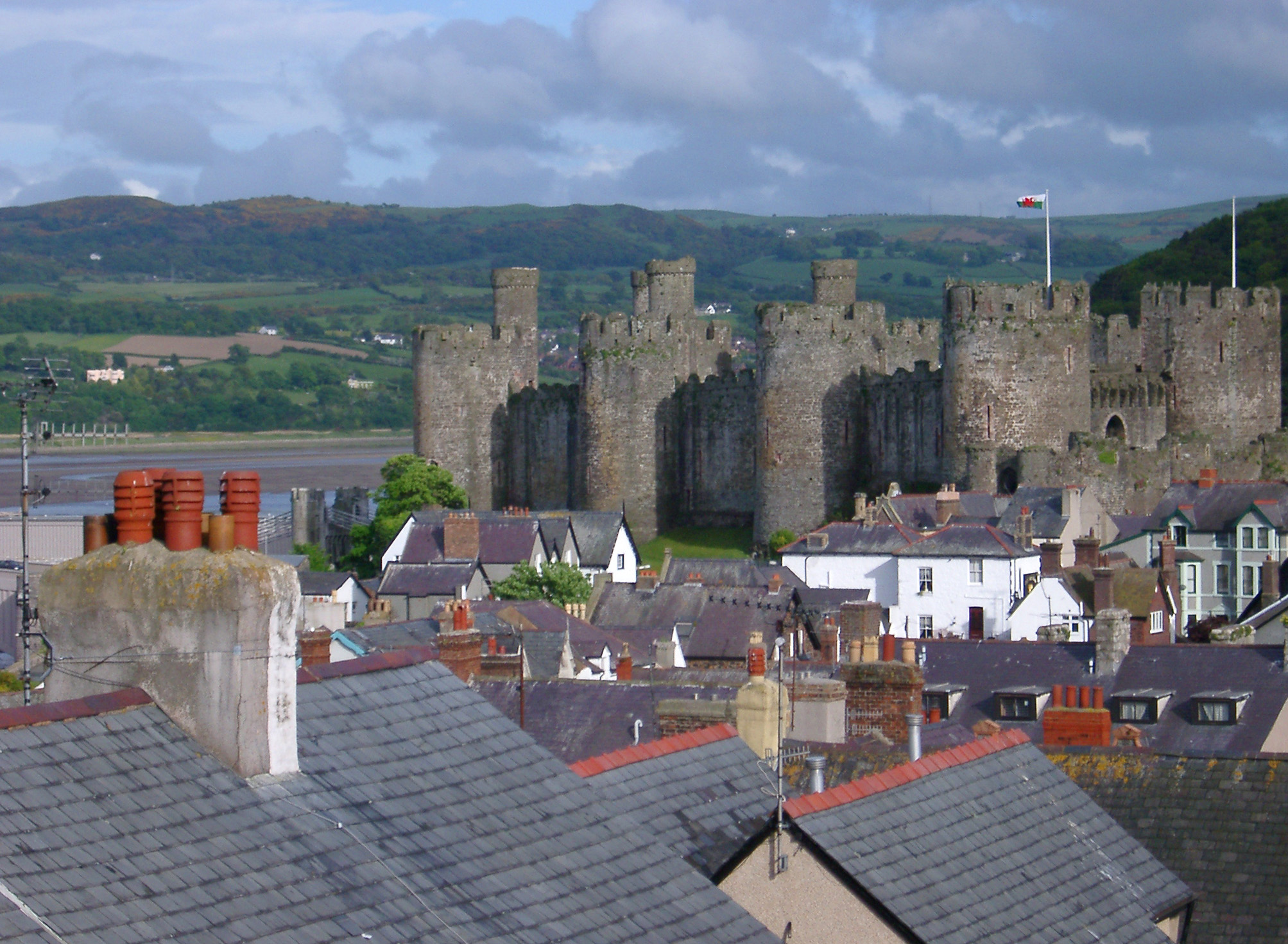 View over Conway rooftops to the historic stone castle and open Welsh countryside behind