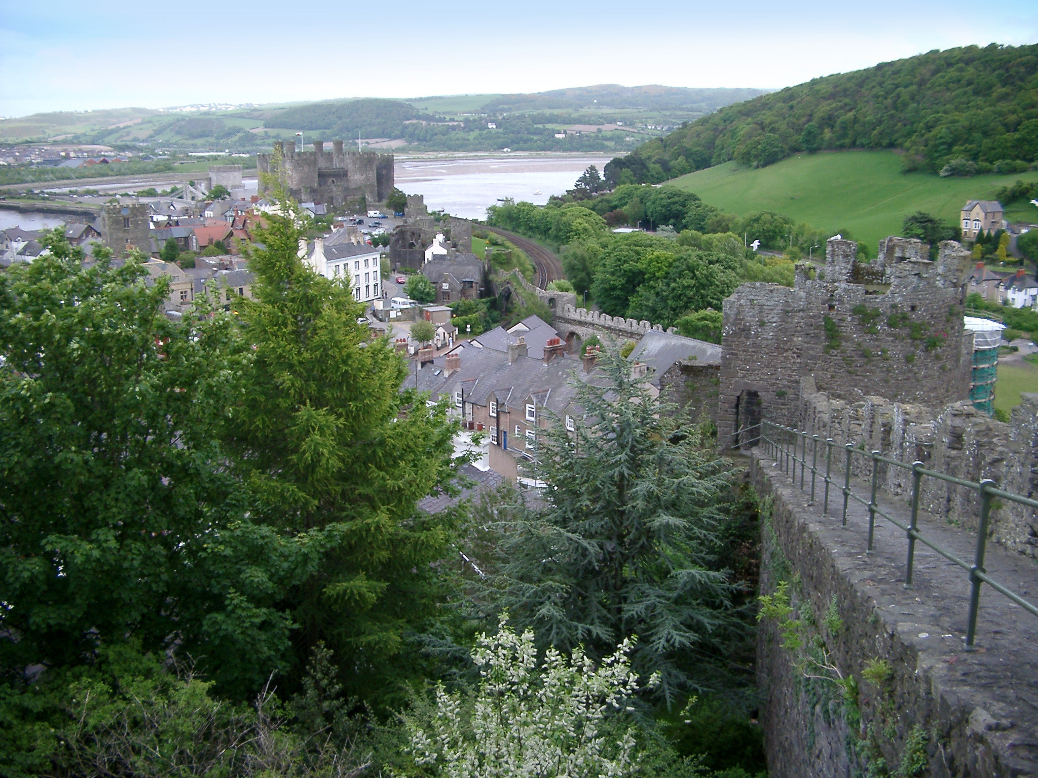 Historic crenellated stone walls surrounding the walled town of Conway, Wales with a scenic view down to the coast