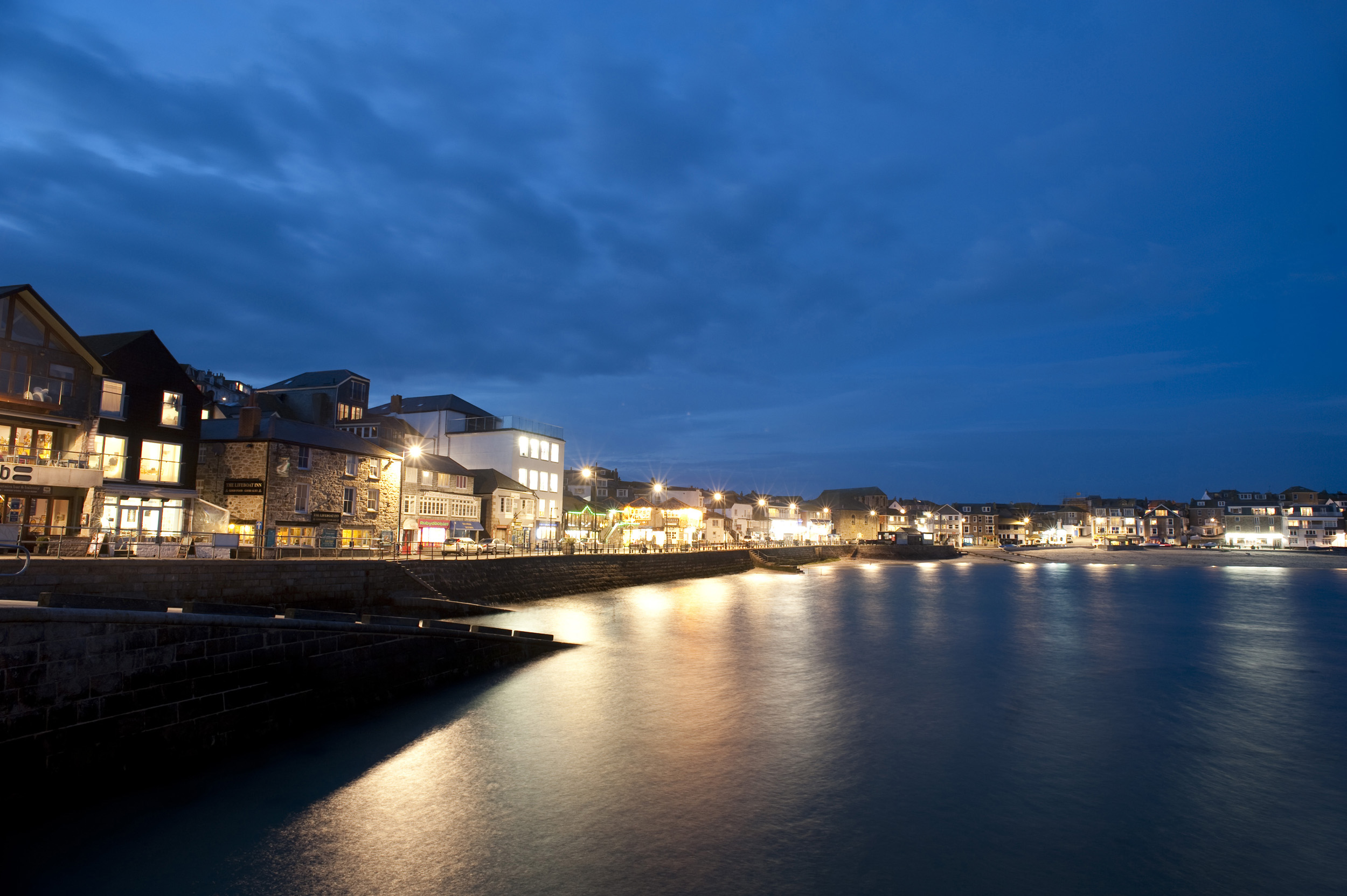 a night time view of the quayside of saint ives harbour, cornwall