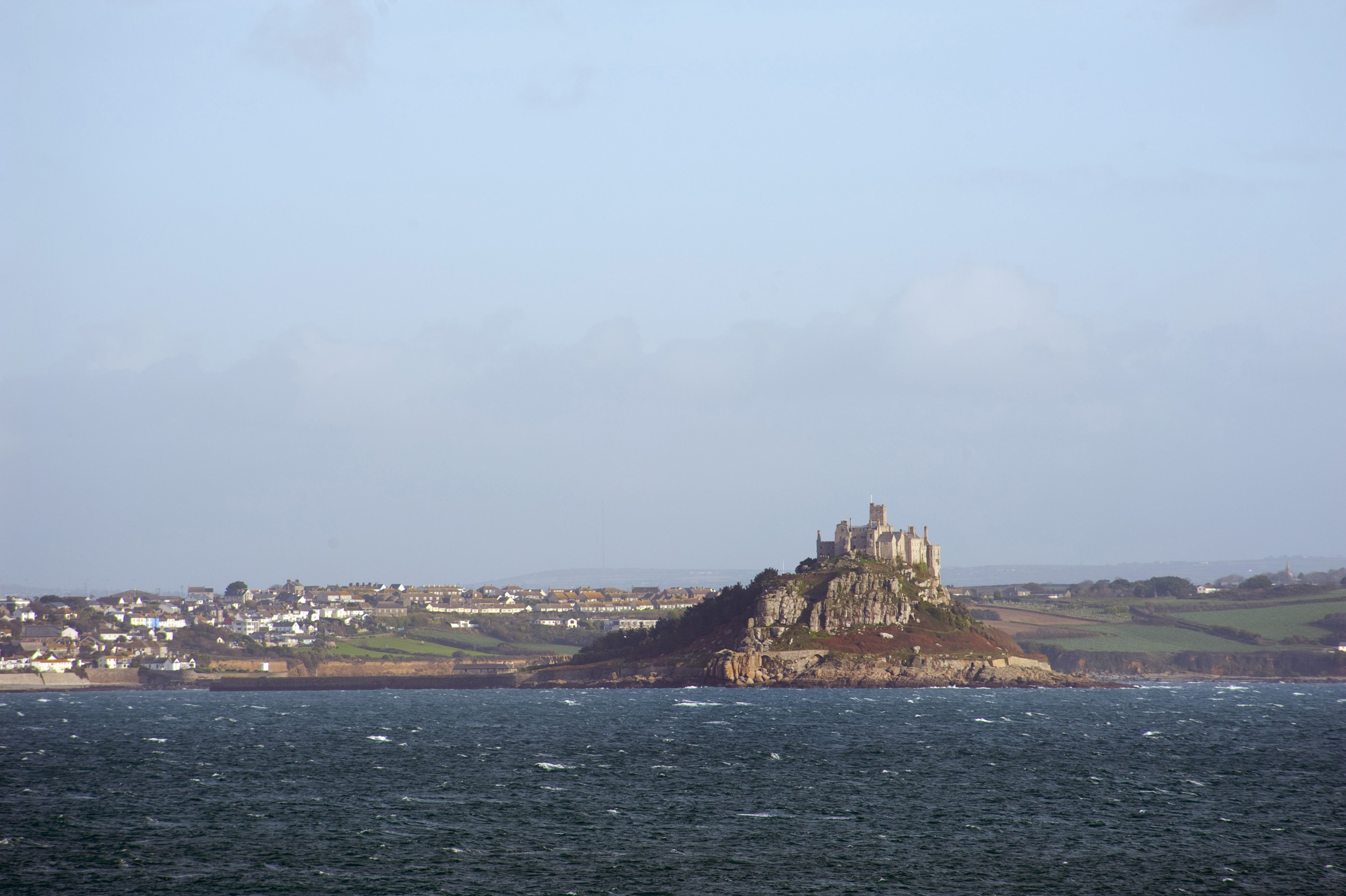 a view of the back of saint michaels mount taken from across the water and town of marazion