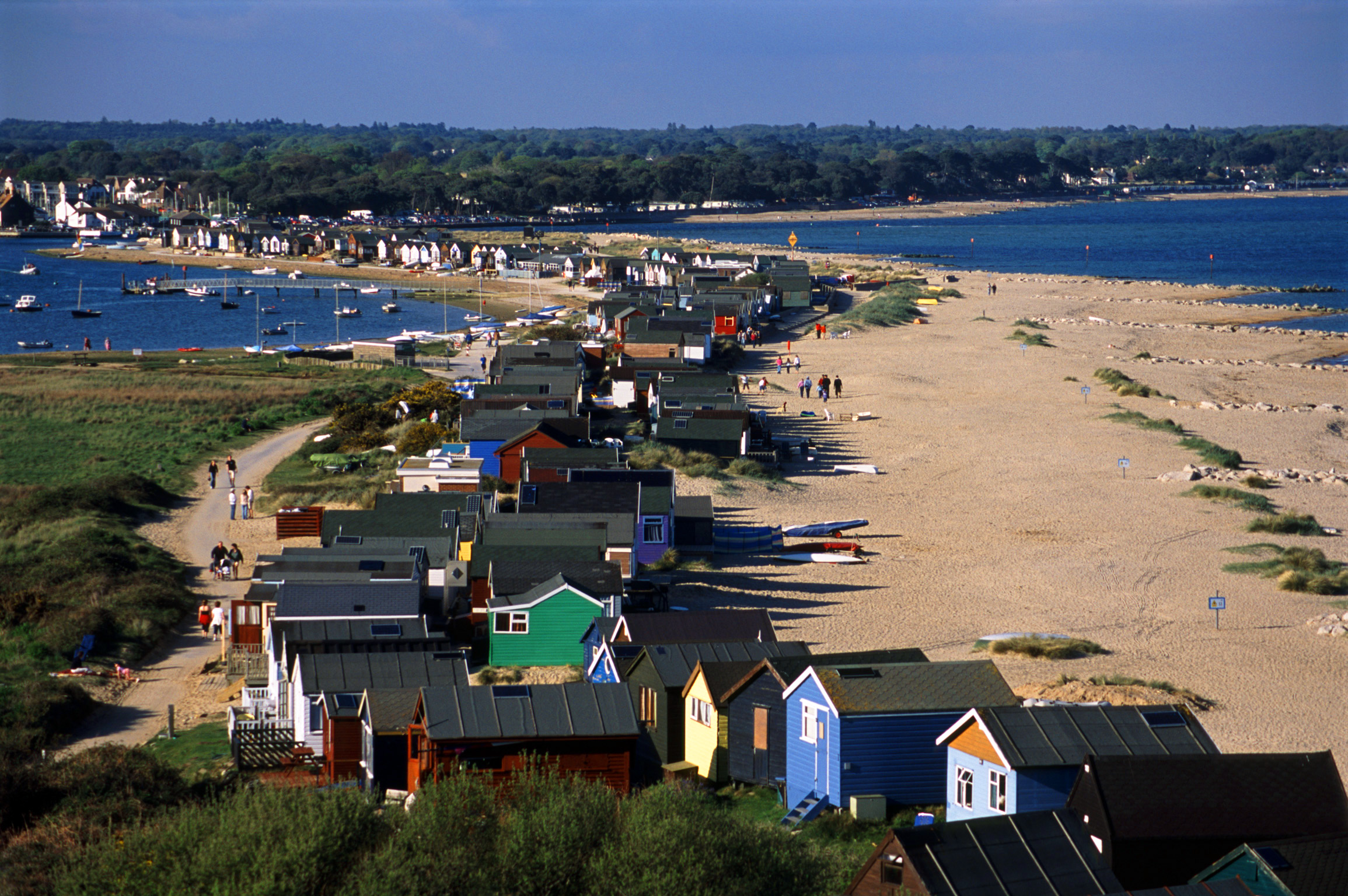 line of beach huts on the mudeford sand spit, christchurch harbour, dorset