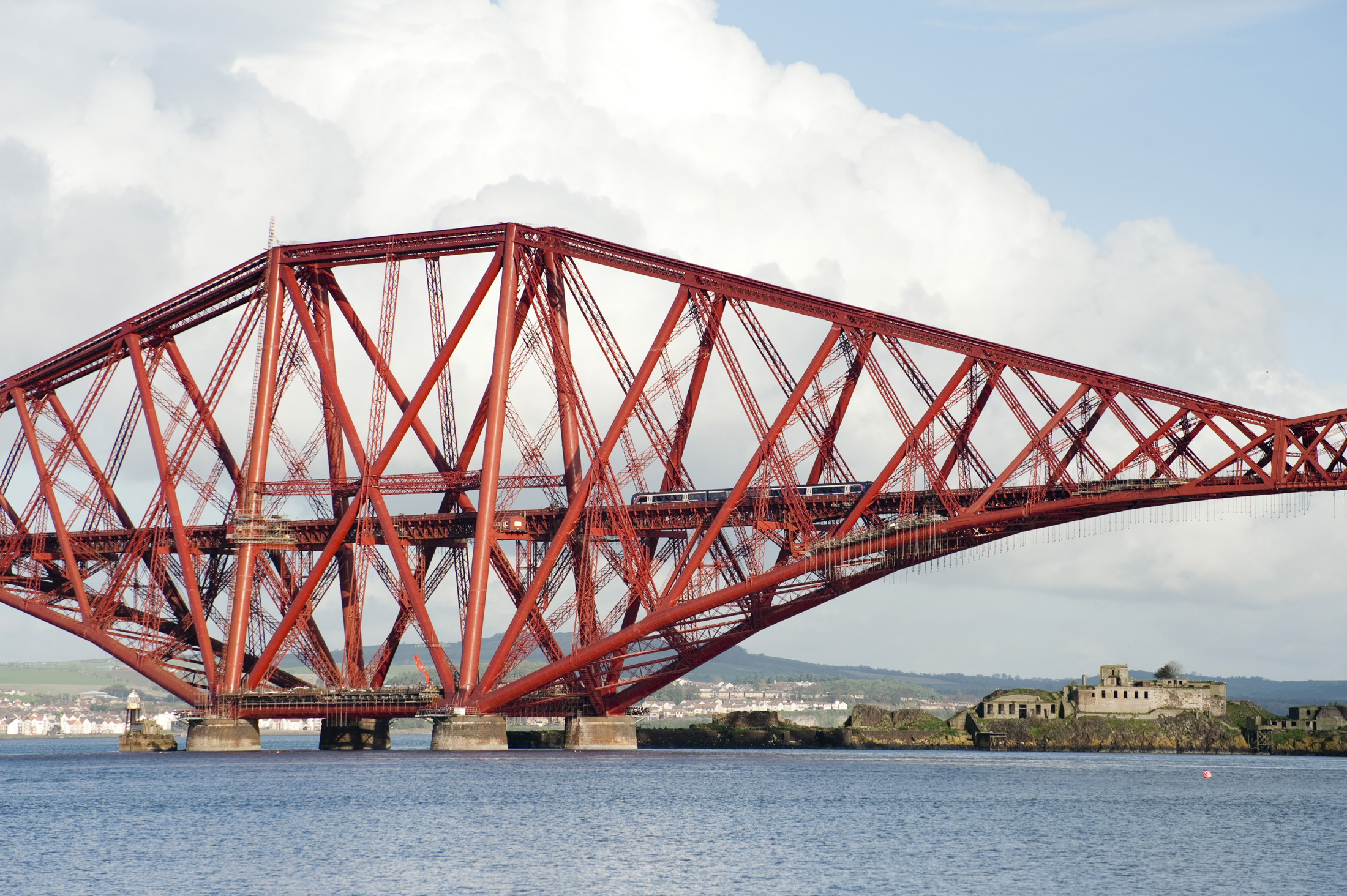 a train dwarfed by the giant structure of the forth bridge, firth of forth, scotland