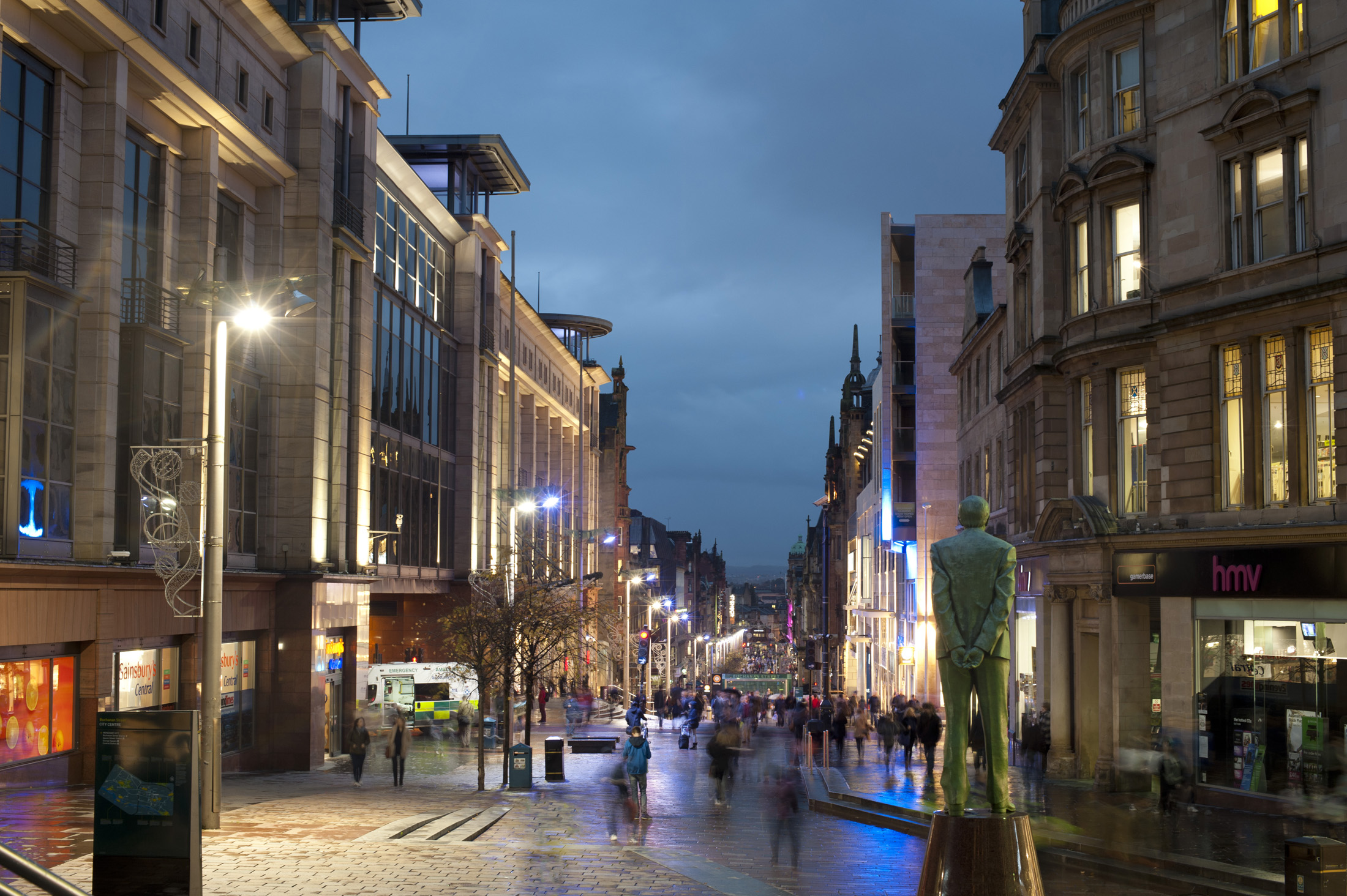 Buchanan Street in Glasgow at night lined with colourful shops and pedestrian shoppers walking the sidewalks