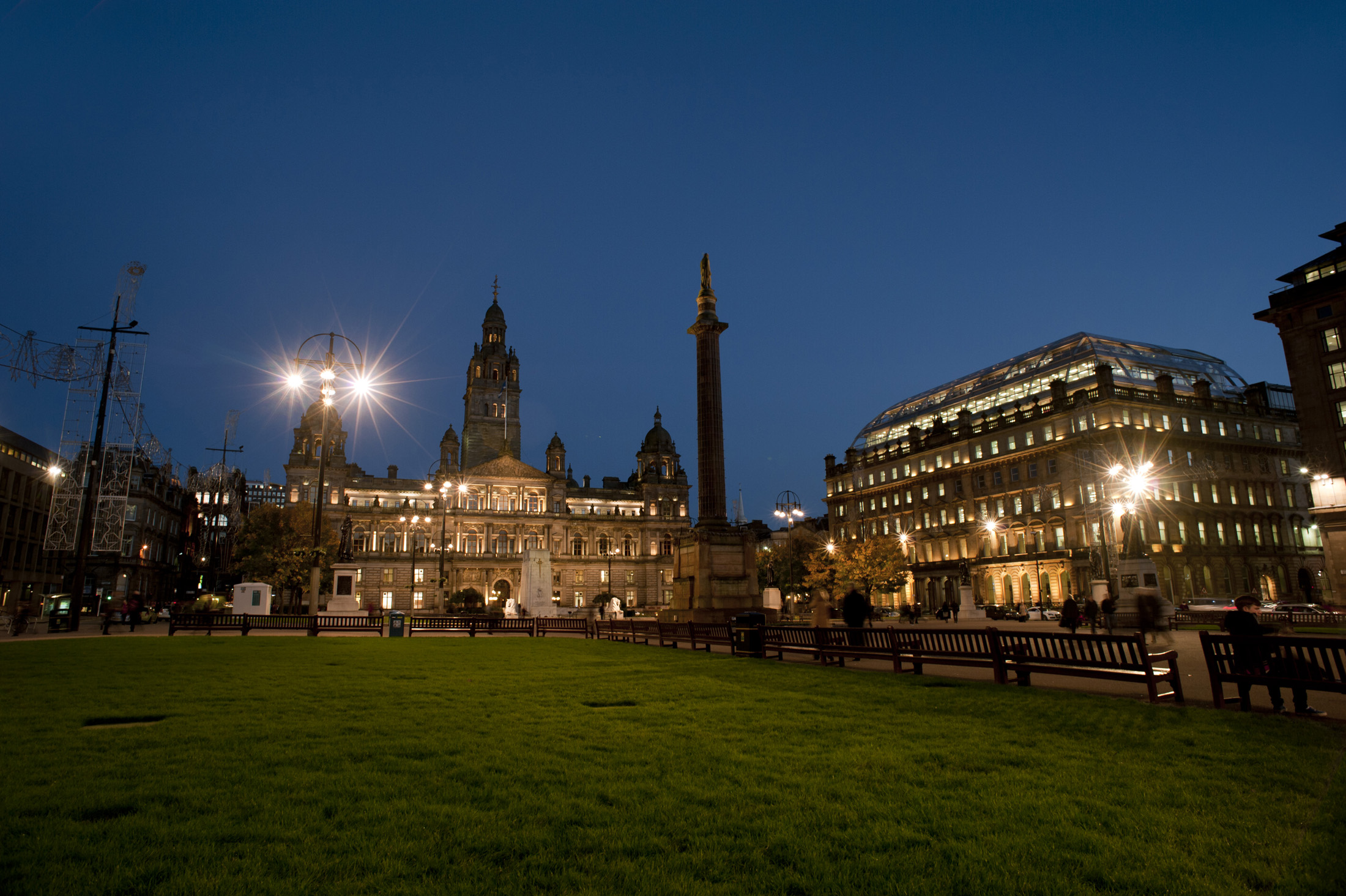 George Square in Glasgow at night with lights illuminating the historical buildings of the Glasgow City Council