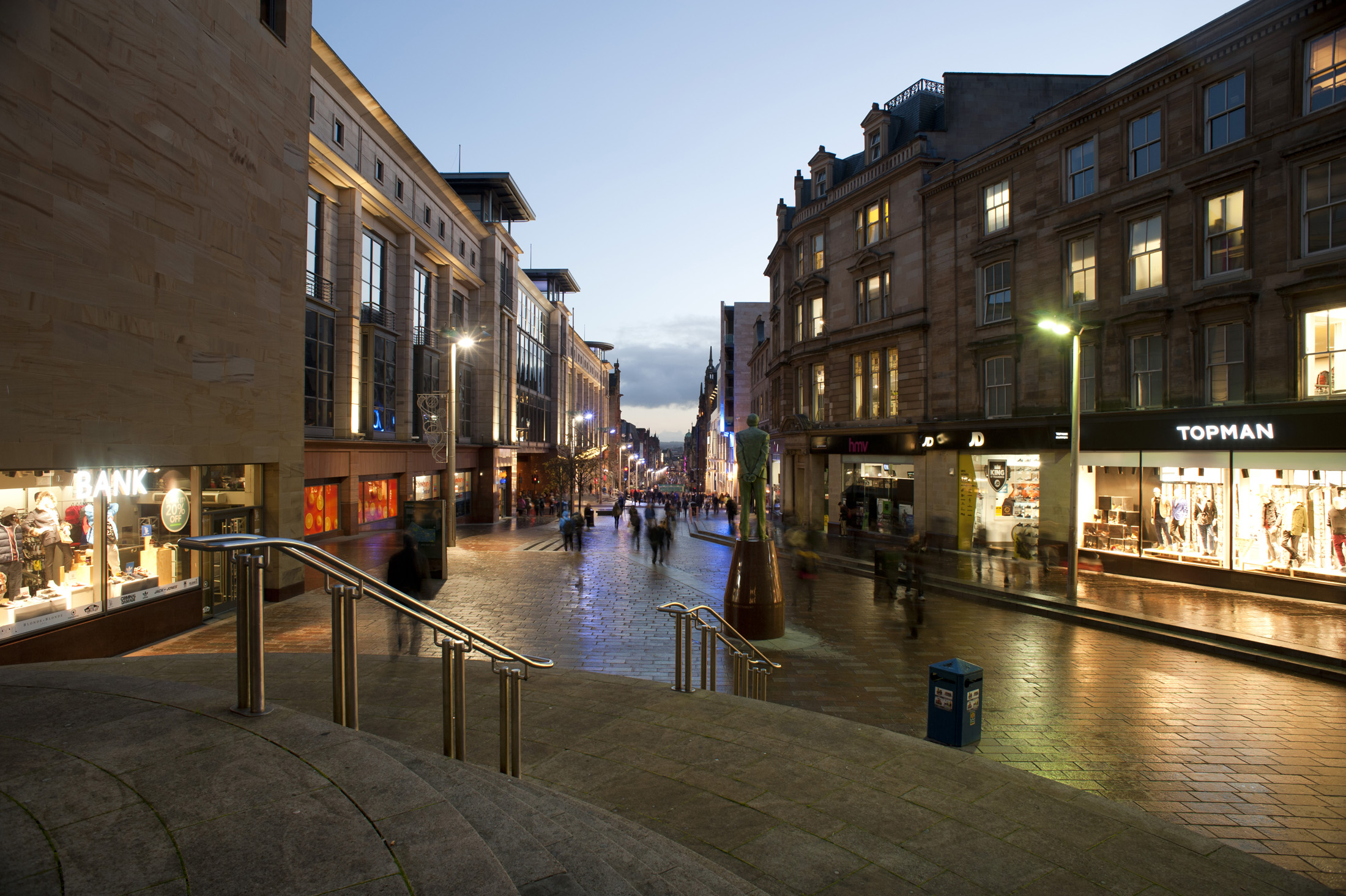 Buchanan Street in central Glasgow at night with the windows of the shops illuminated with bright lights reflected on the street below