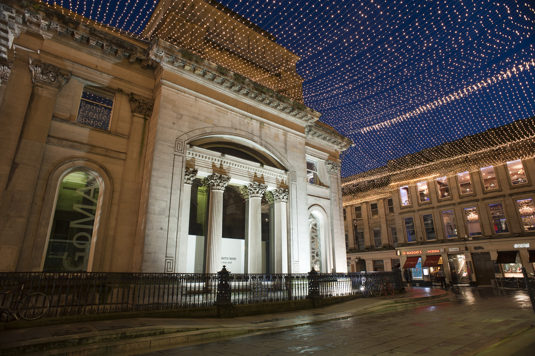 Royal Exchange Square and the GOMA, or Gallery of Modern Art, building in Glasgow illuminated at night with a display of overhead Christmas lights