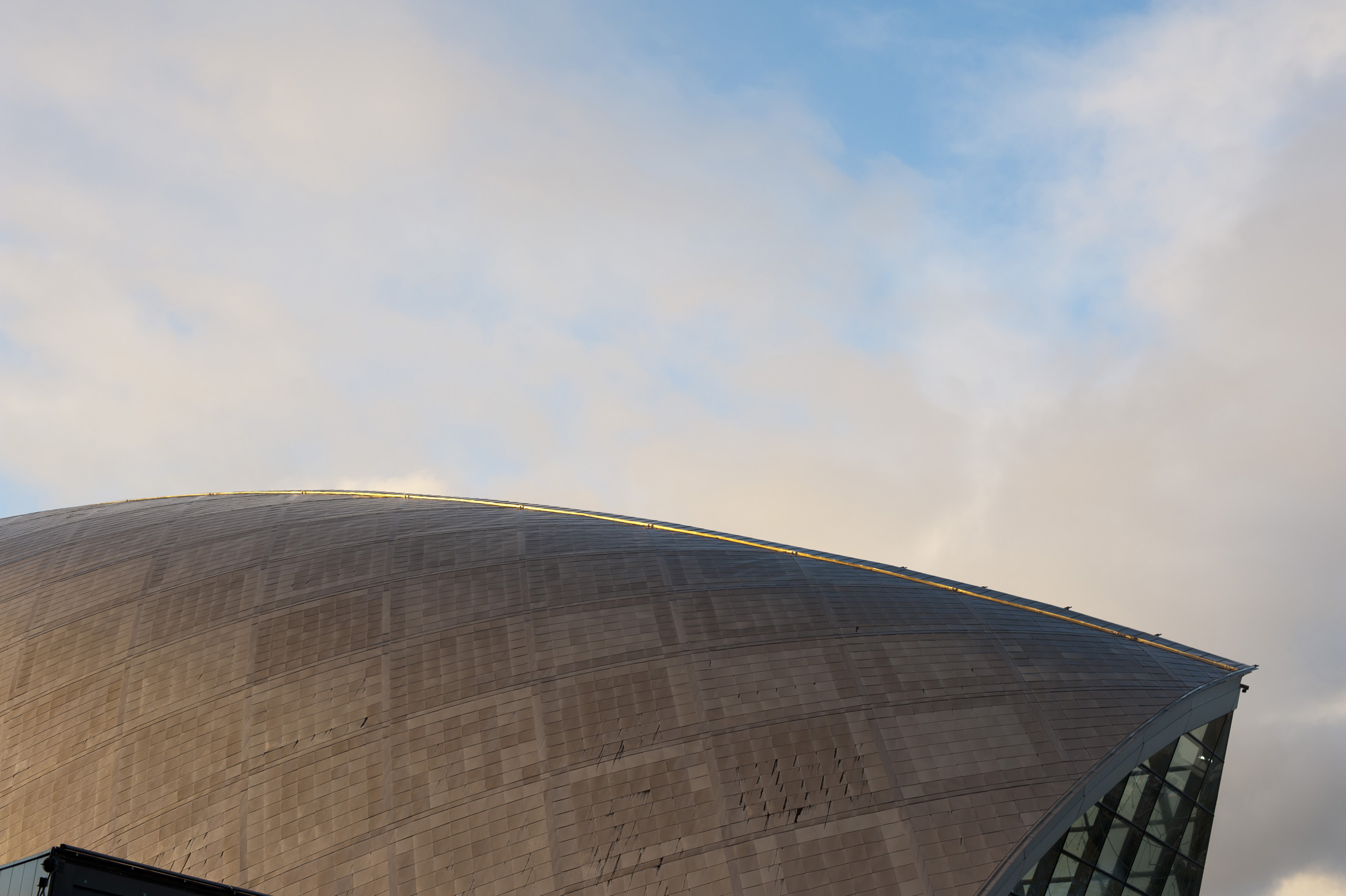 Detail of the architecture of the external facade of the Glasgow Science Centre with its distinctive domed metal structure against a blue sky