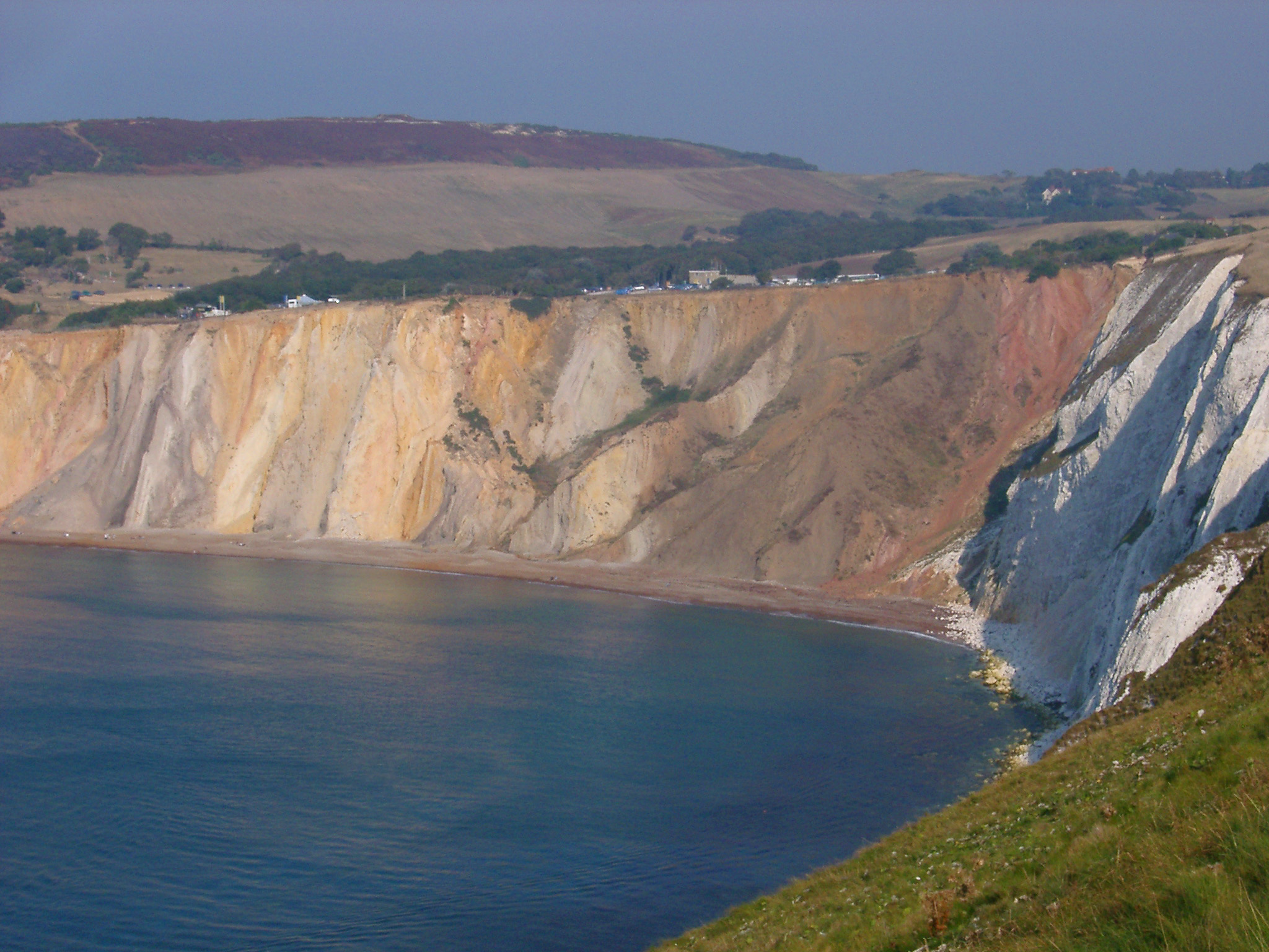 View along the scenic coastline of the Alum Bay cliffs, Isle of Wight showing erosion of color of the chalk with a calm ocean below