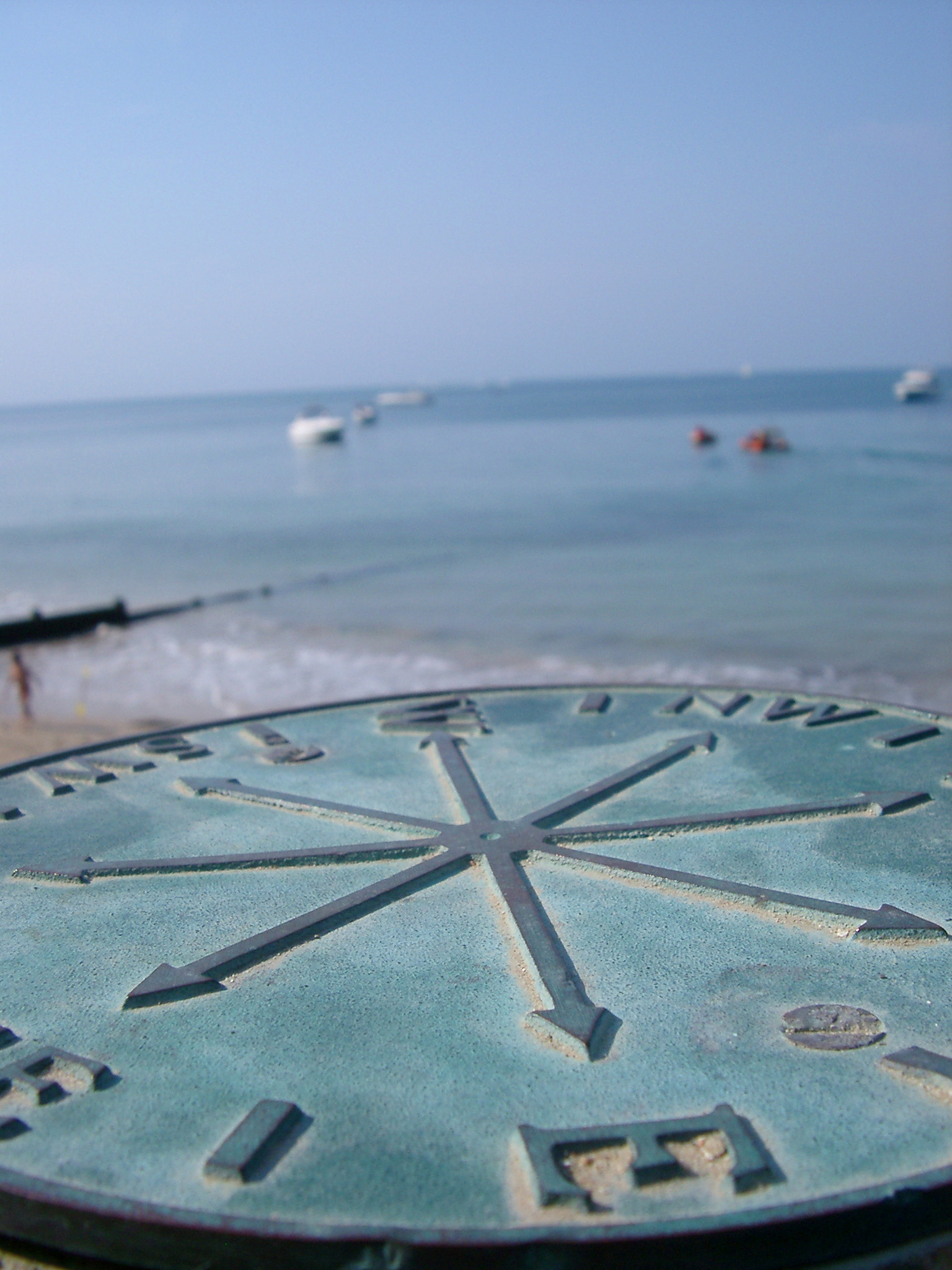 Low angle view over the dial showing the compass points of a brass marine compass overlooking the ocean and moored small boats