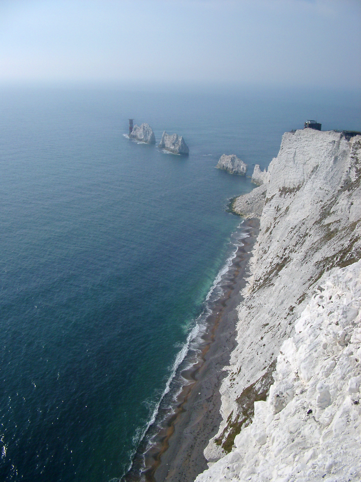 View along the coastline of the Isle of Wight showing the steep cliffs, beach and the Needles, a row of eroded chalk stacks rising from the ocean