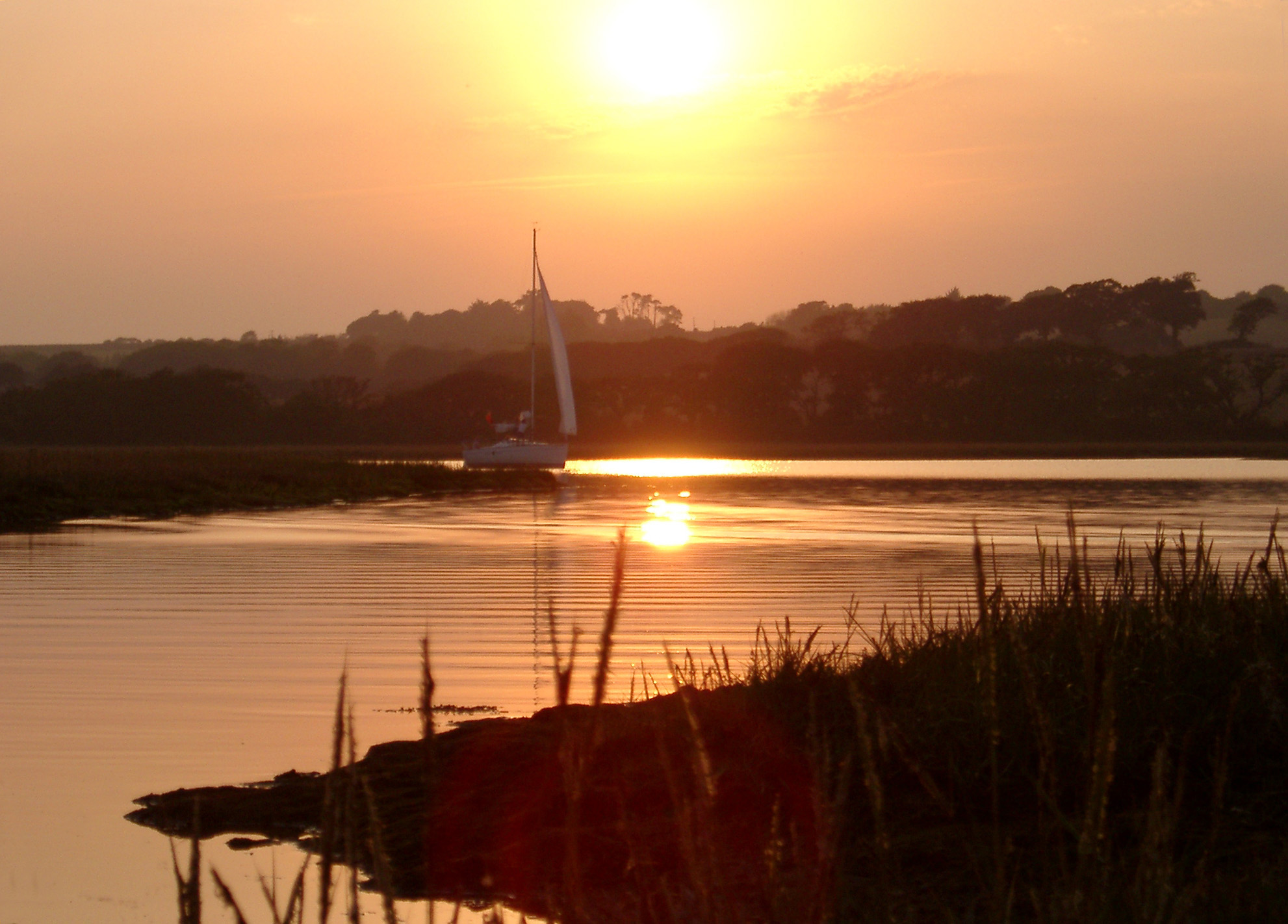 River Yar, Isle of Wight, which starts at Freshwater Bay, on the south coast of the island and flows only a few miles north to Yarmouth viewed at sunset with the orange sun reflected in the calm water