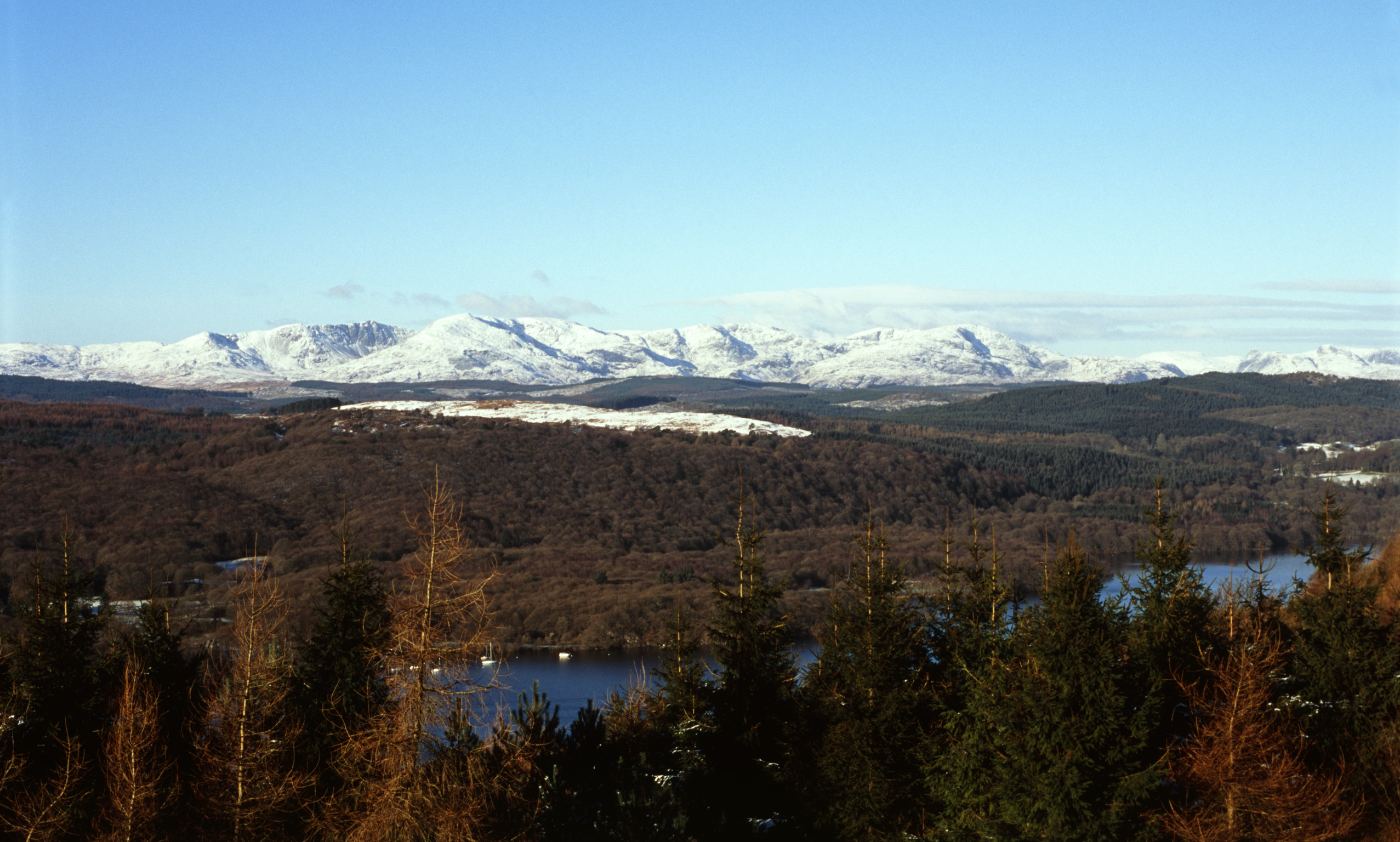 panoramic view of the hills around lake windermere with peaks capped by winter snow