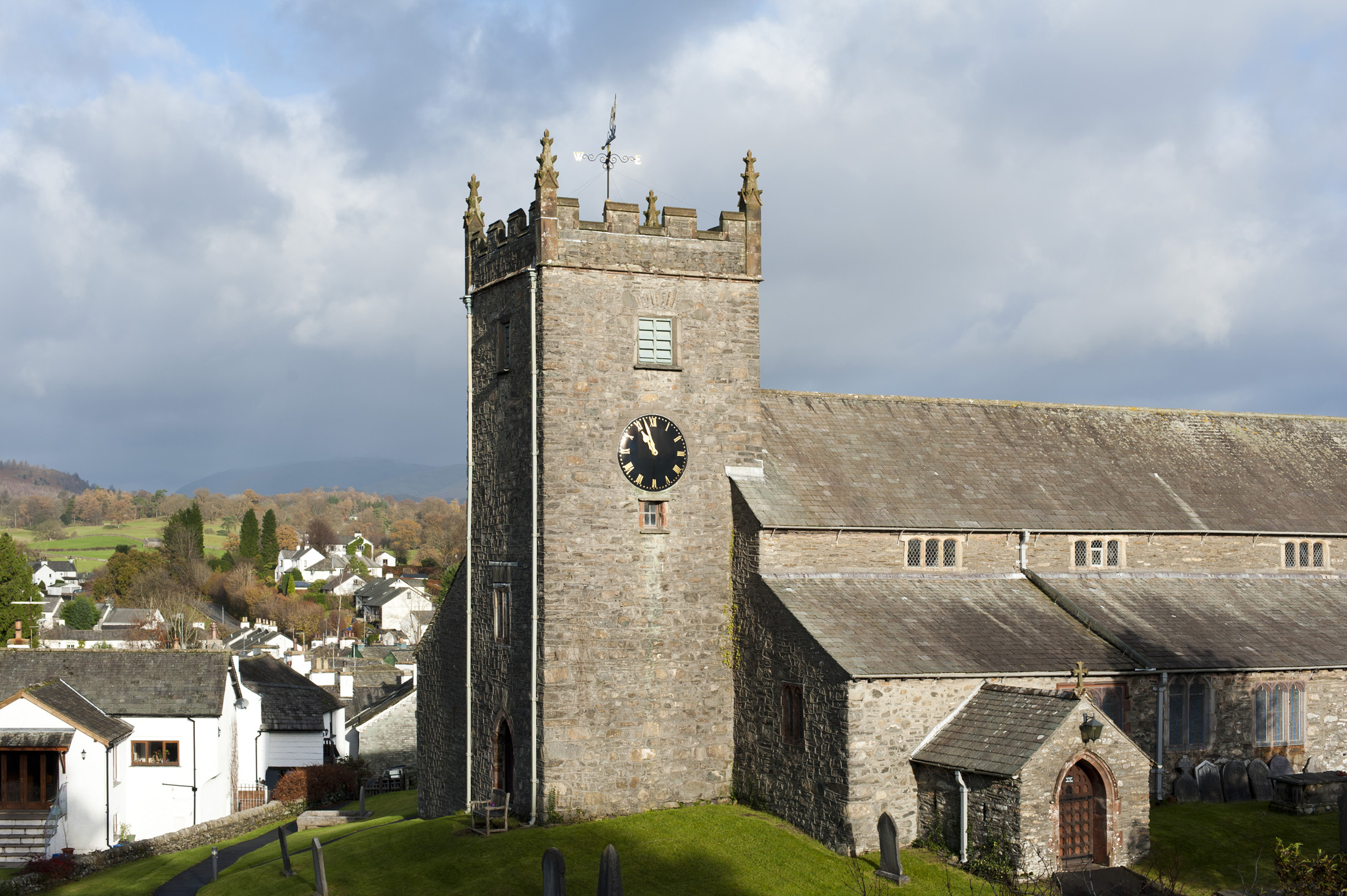 View of the old stone building and clock tower of St Michael and All Angels Church in the quaint whitewashed village of Hawkshead in the Lake District in Cumbria