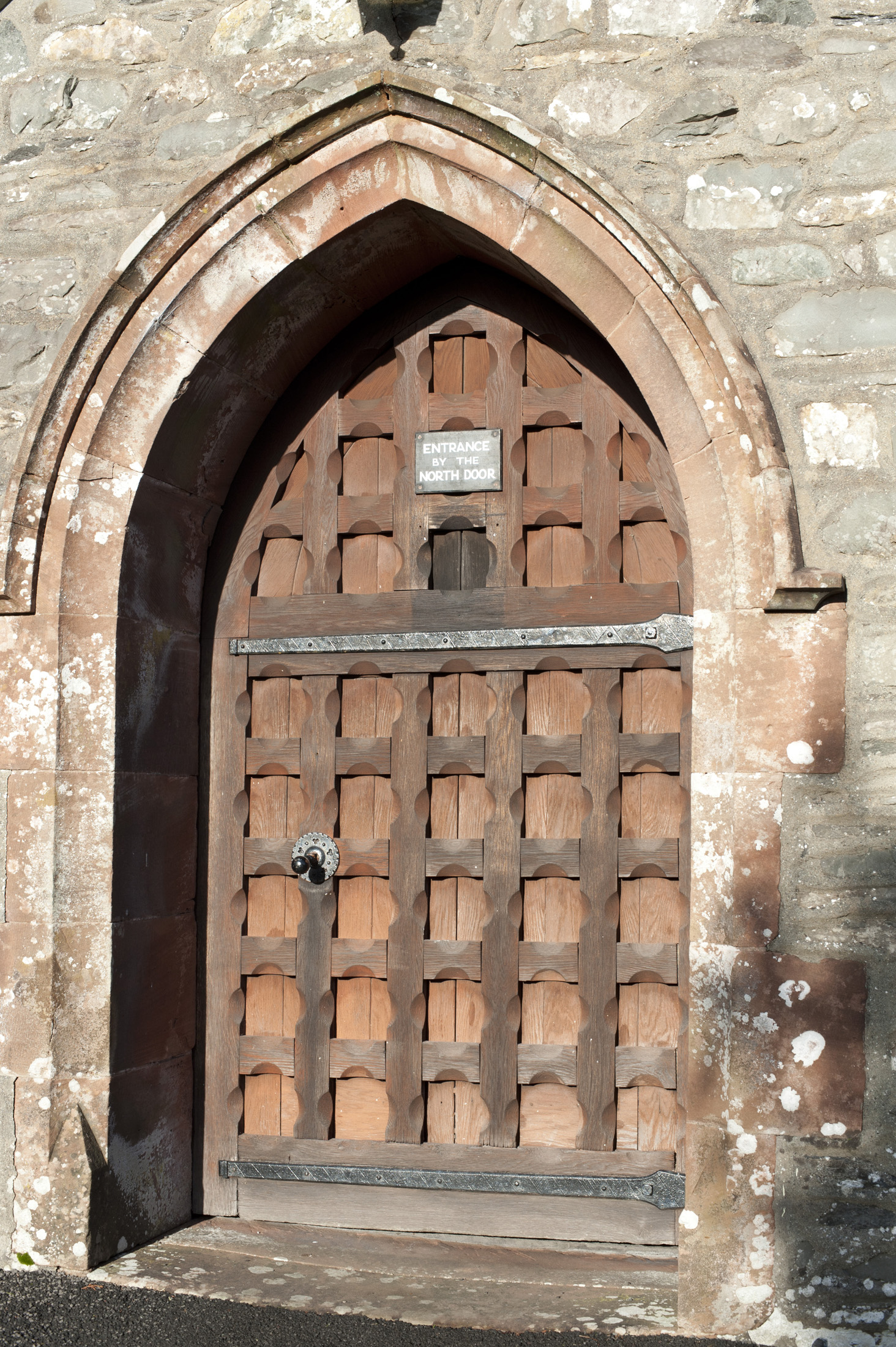 Arched medieval wooden entrance door to St Michaels and All Angels Church in the village of Hawkshead in the Lake District in Cumbria
