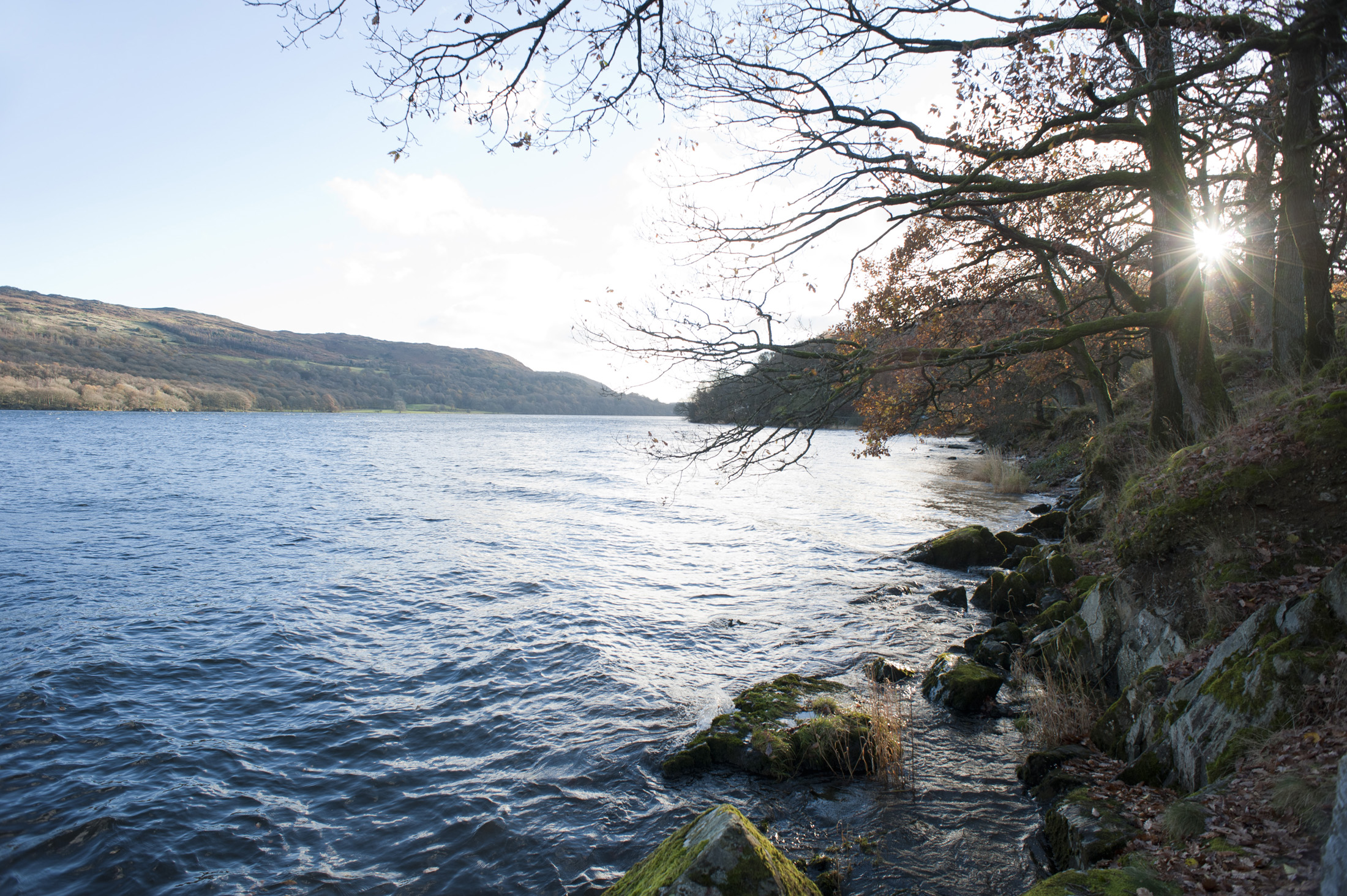 sun glinting over the surface of coniston water in the english lake district