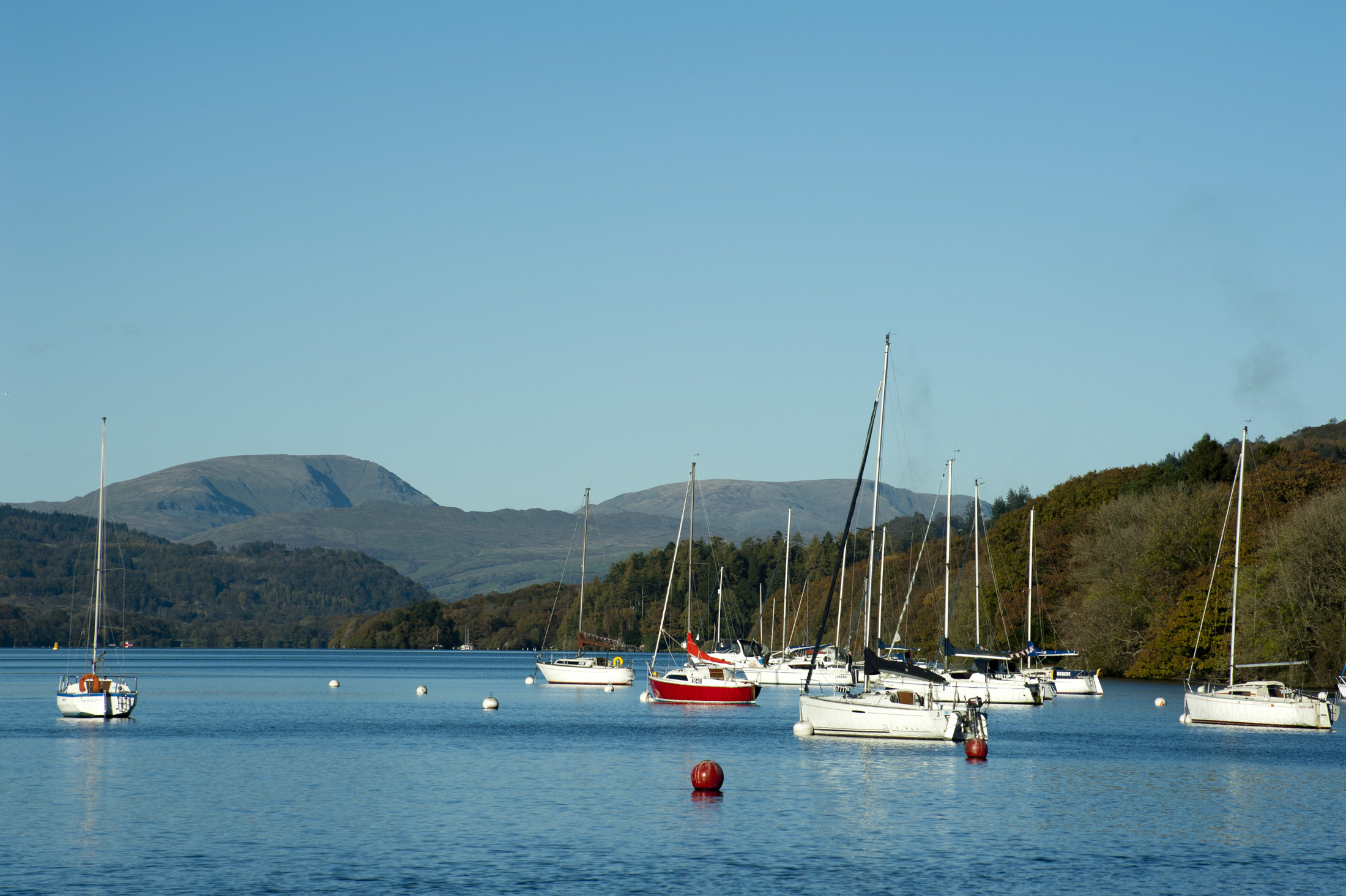 Yachts moored to buoys on the calm water of the lake at Windermere in the Lake District in Cumbria