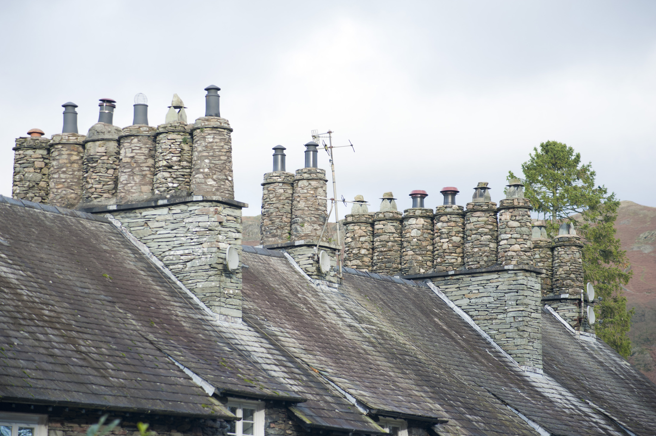 Roofs and traditional cylindrical chimney pots constructed of stone on Cumbrian cottages in the Lake District
