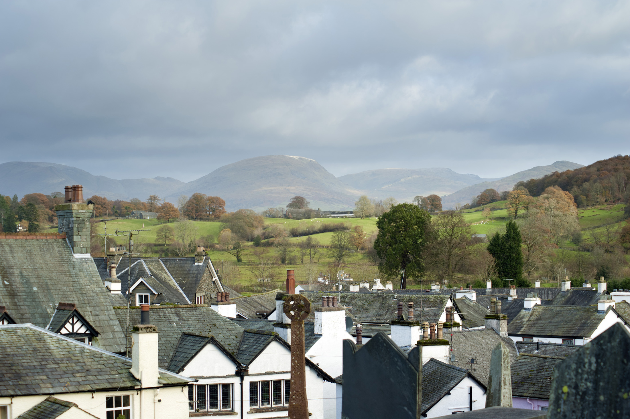 Panoramic view of Hawkshead in Cumbria with its picturesque whitewashed cottages surrounded by lush countryside with mountins and rolling hills, a popular tourist destination in the Lake District