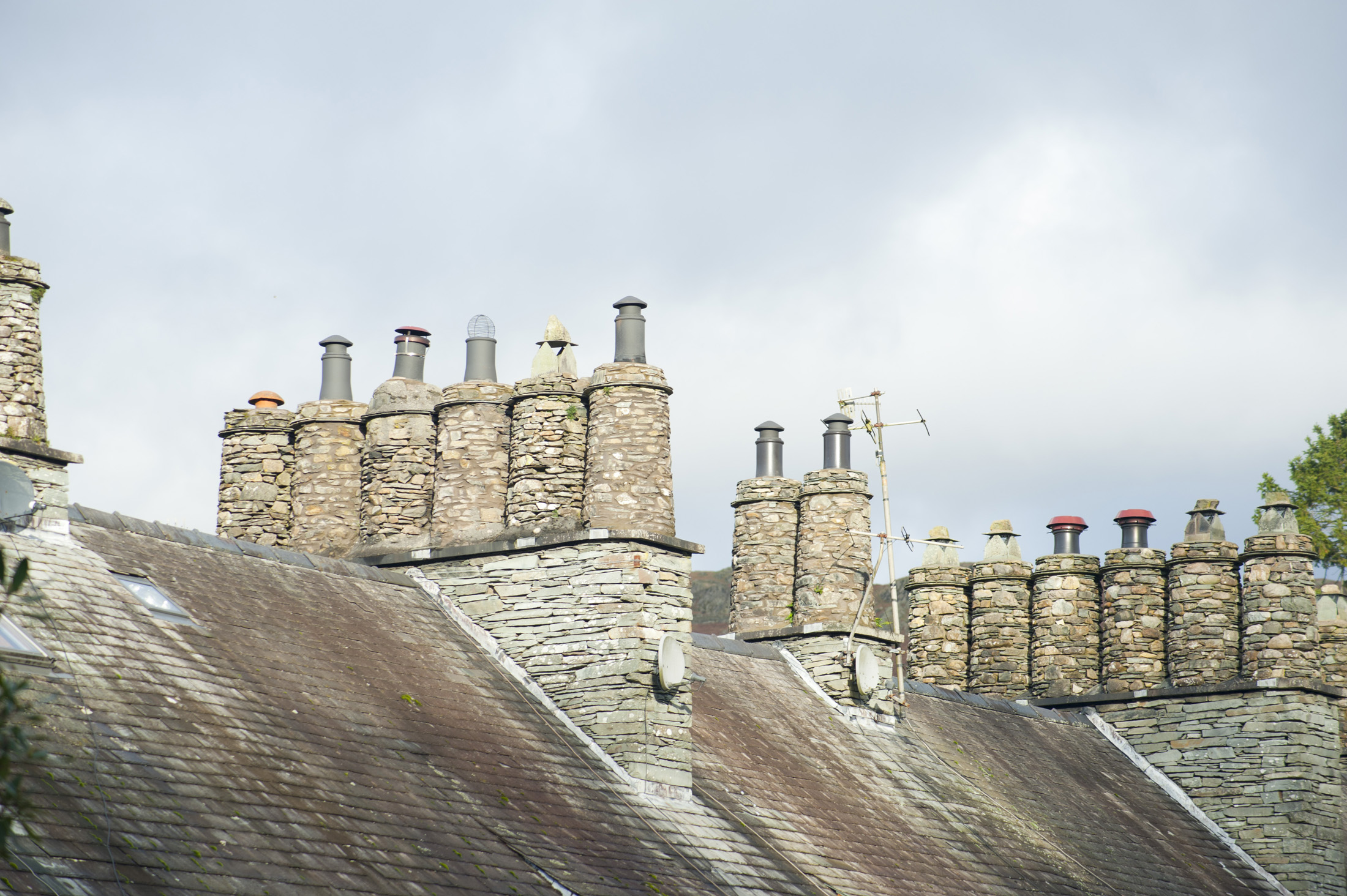 Traditional cylindrical stone chimney pots on the rooftops of the cottages in Skelwith Bridge, a village in the Englsih Lake District in Cumbria