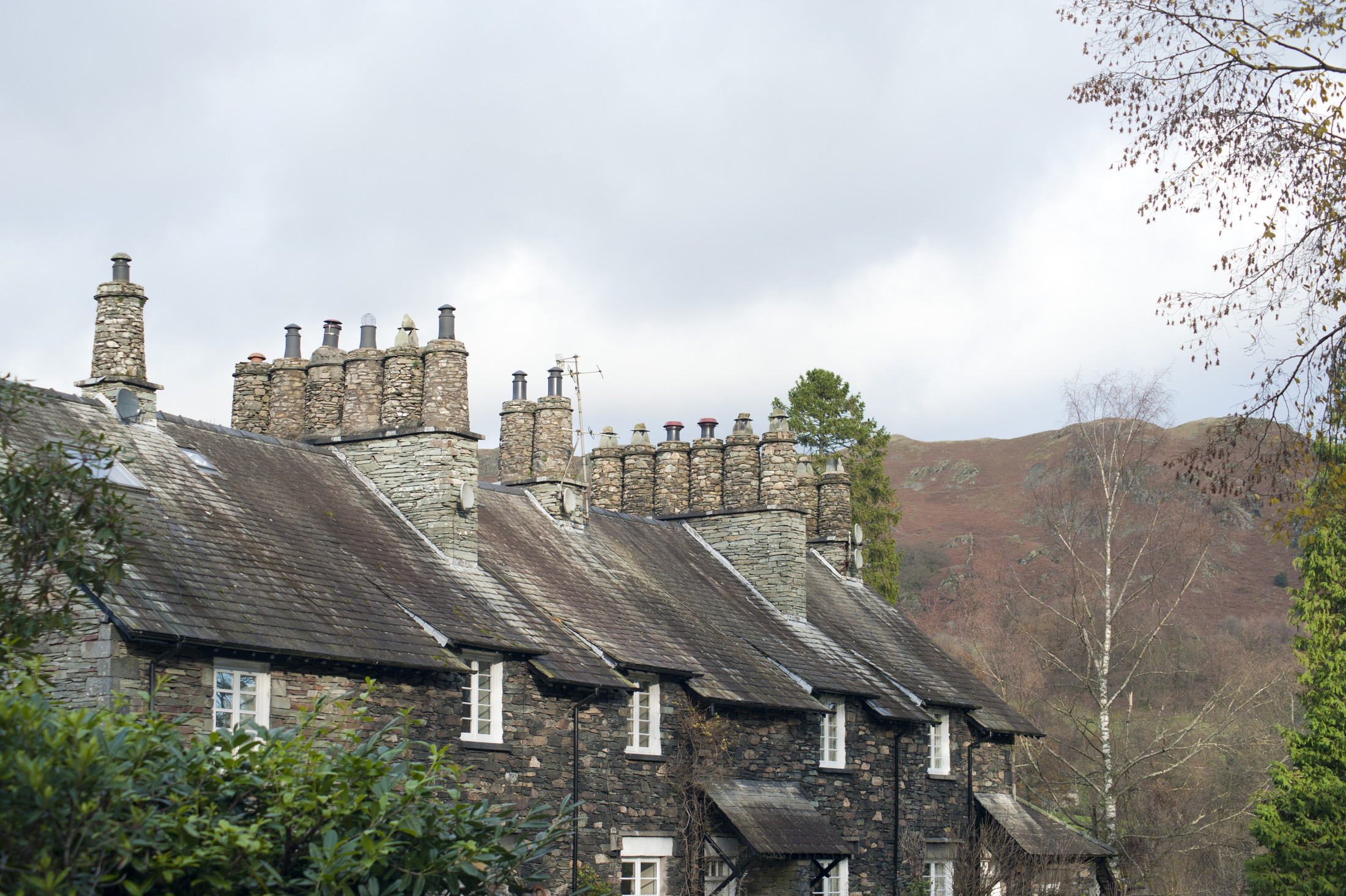 Row of quaint stone cottages at Skelwith Bridge in the Lake District with traditional cylindrical chimney pots made of stone in a leafy green lane